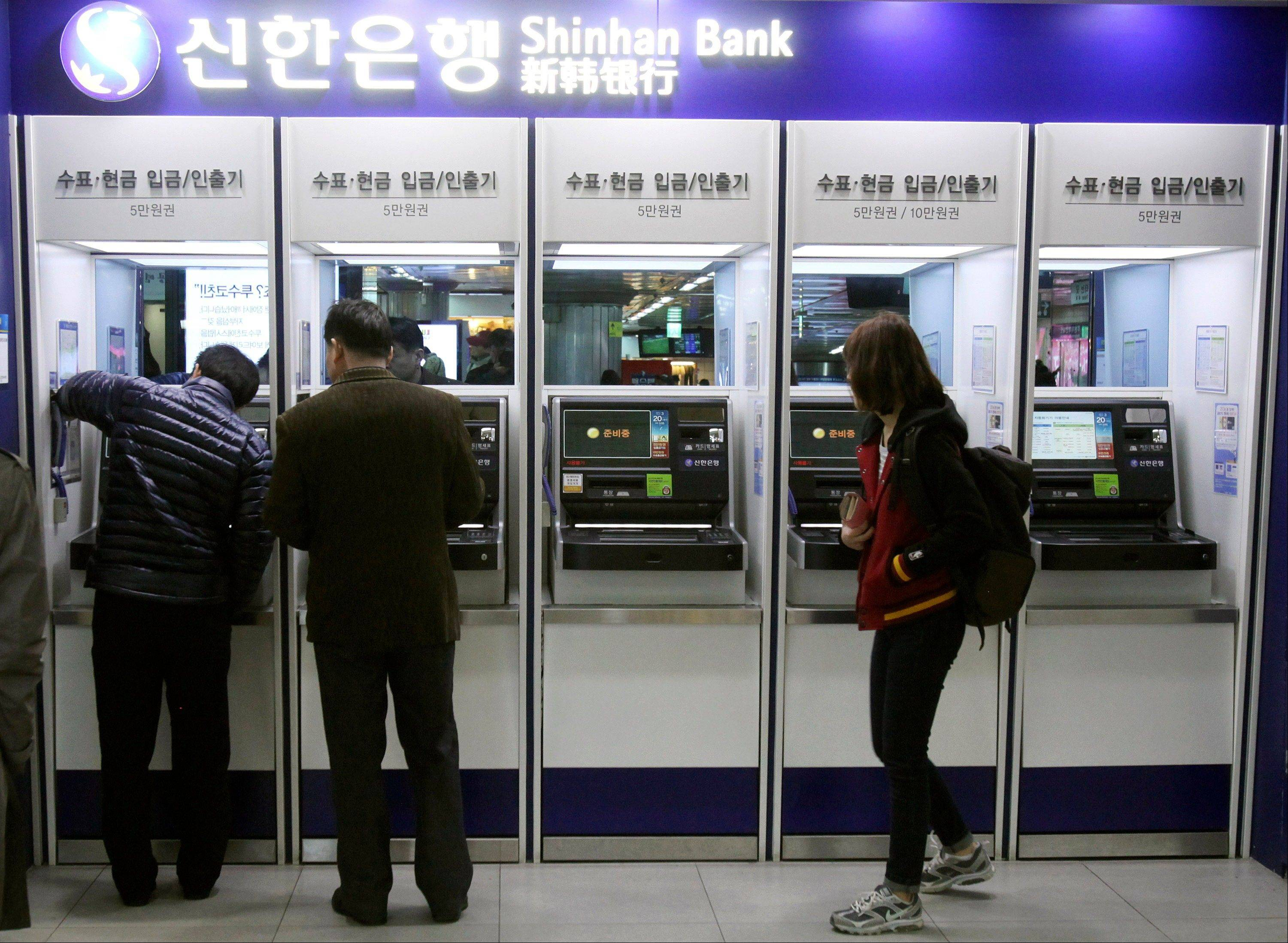 Depositors try to use automated teller machines while the bank�s computer networks are paralyzed at a subway station in Seoul, South Korea, Wednesday. Computer networks at two major South Korean banks and three top TV broadcasters went into shutdown mode en masse Wednesday.