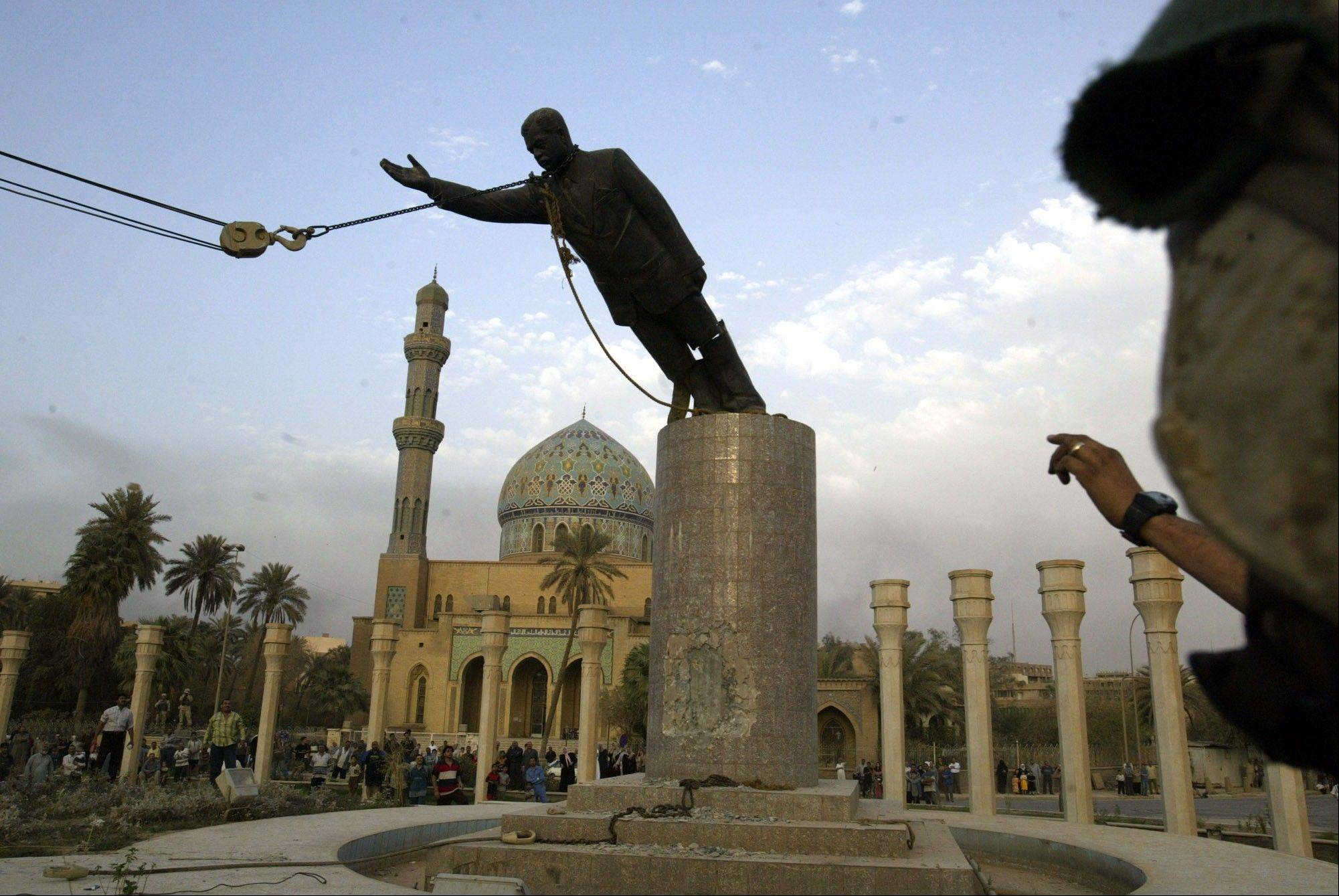 FILE - A U.S. Marine watches a statue of Saddam Hussein being toppled in Firdaus Square in downtown Baghdad on April 9, 2003 file photo.