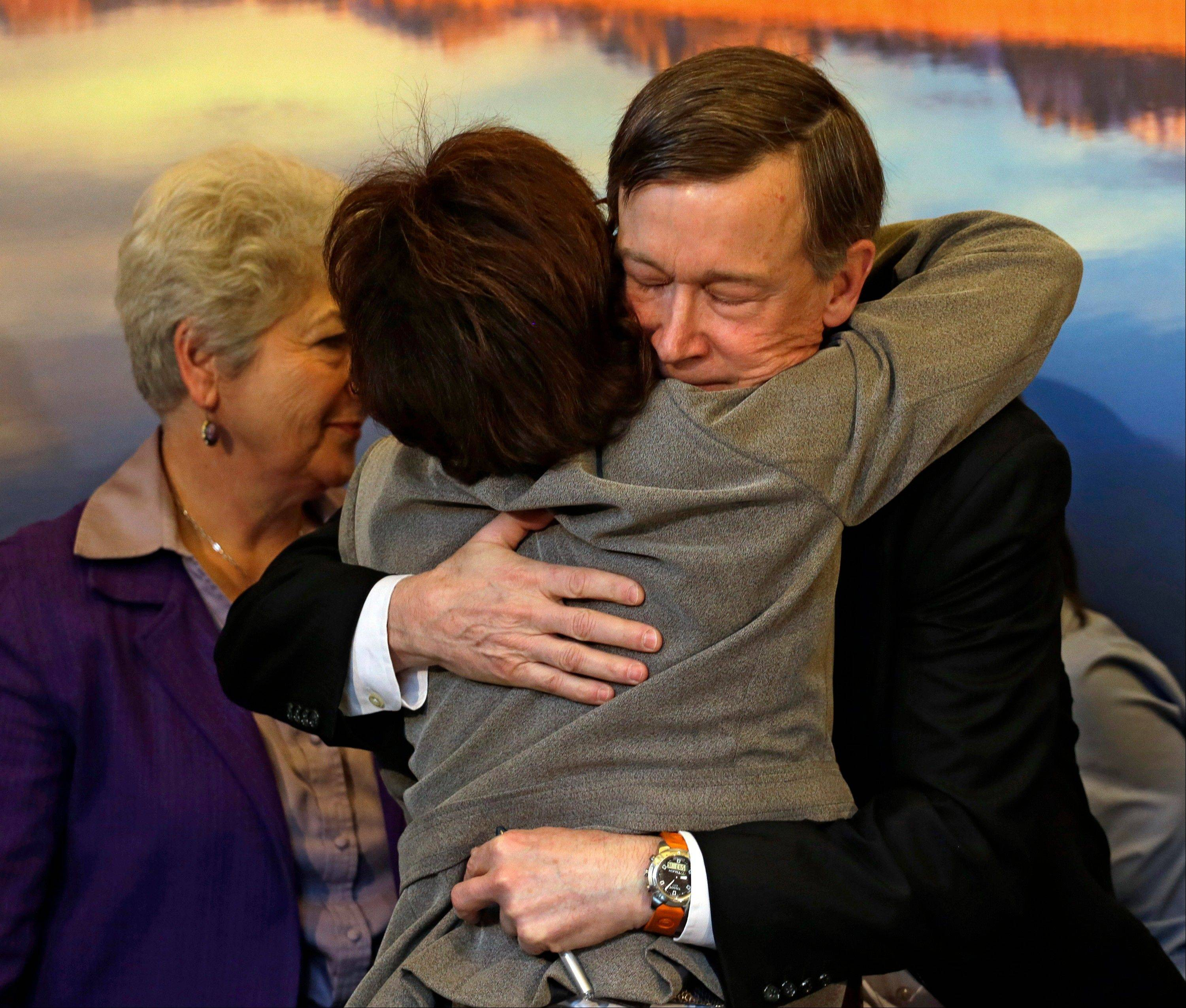Colorado Gov. John Hickenlooper, right, is hugged by Colorado Rep. Rhonda Fields after he signed gun control bills into law at the Capitol in Denver on Wednesday. Fields was a co-sponsor of bills on background checks and the size of ammunition magazines.