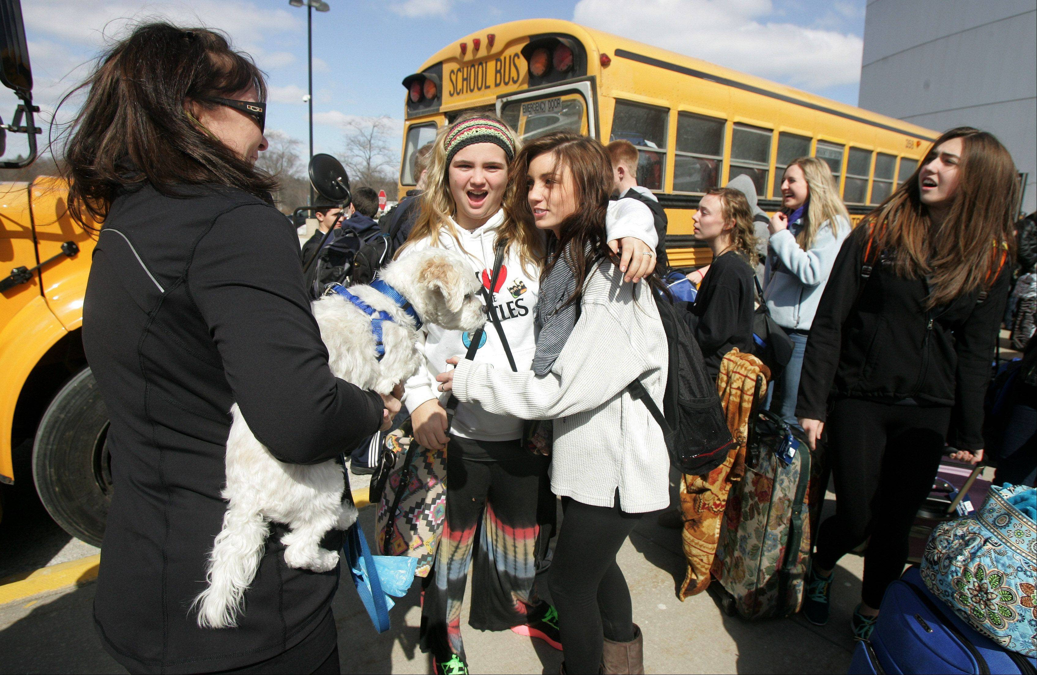 Jan Zobel, left, brings her dog, Max, to see Danielle Dicosola and her daughter, Riley, as Lake Zurich High School choir students leave Wednesday to travel to Italy. They�ll perform during Mass at St. Peter�s Basilica in Vatican City.