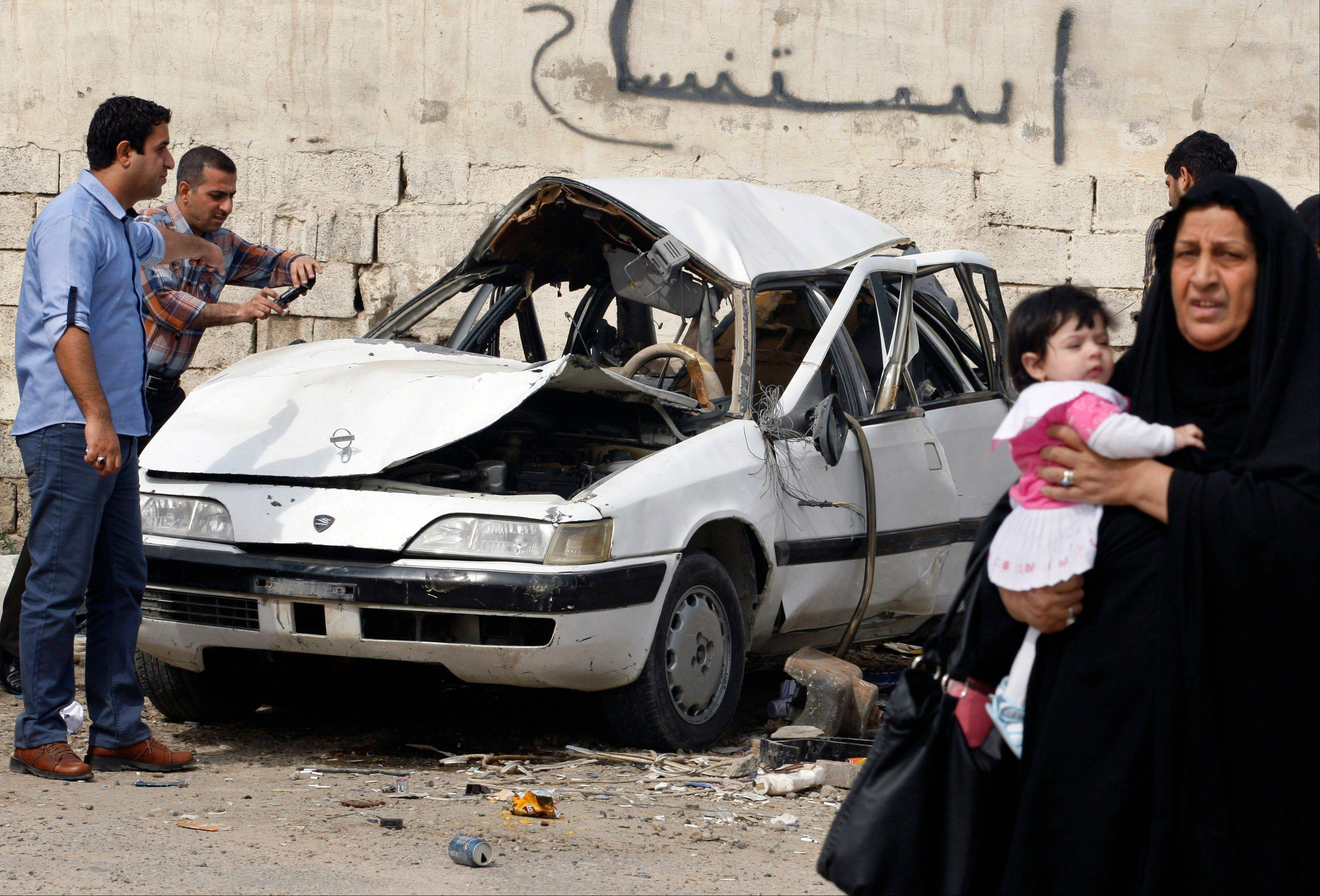 People inspect a damaged car at the scene of a car-bomb attack in Zayona neighborhood of eastern Baghdad, Iraq, Wednesday, March 20, 2013. An al-Qaida-affiliated group in Iraq claimed responsibility for bloody attacks that killed dozens of people across the country on Tuesday, the eve of the 10th anniversary of the 2003 U.S.-led invasion.