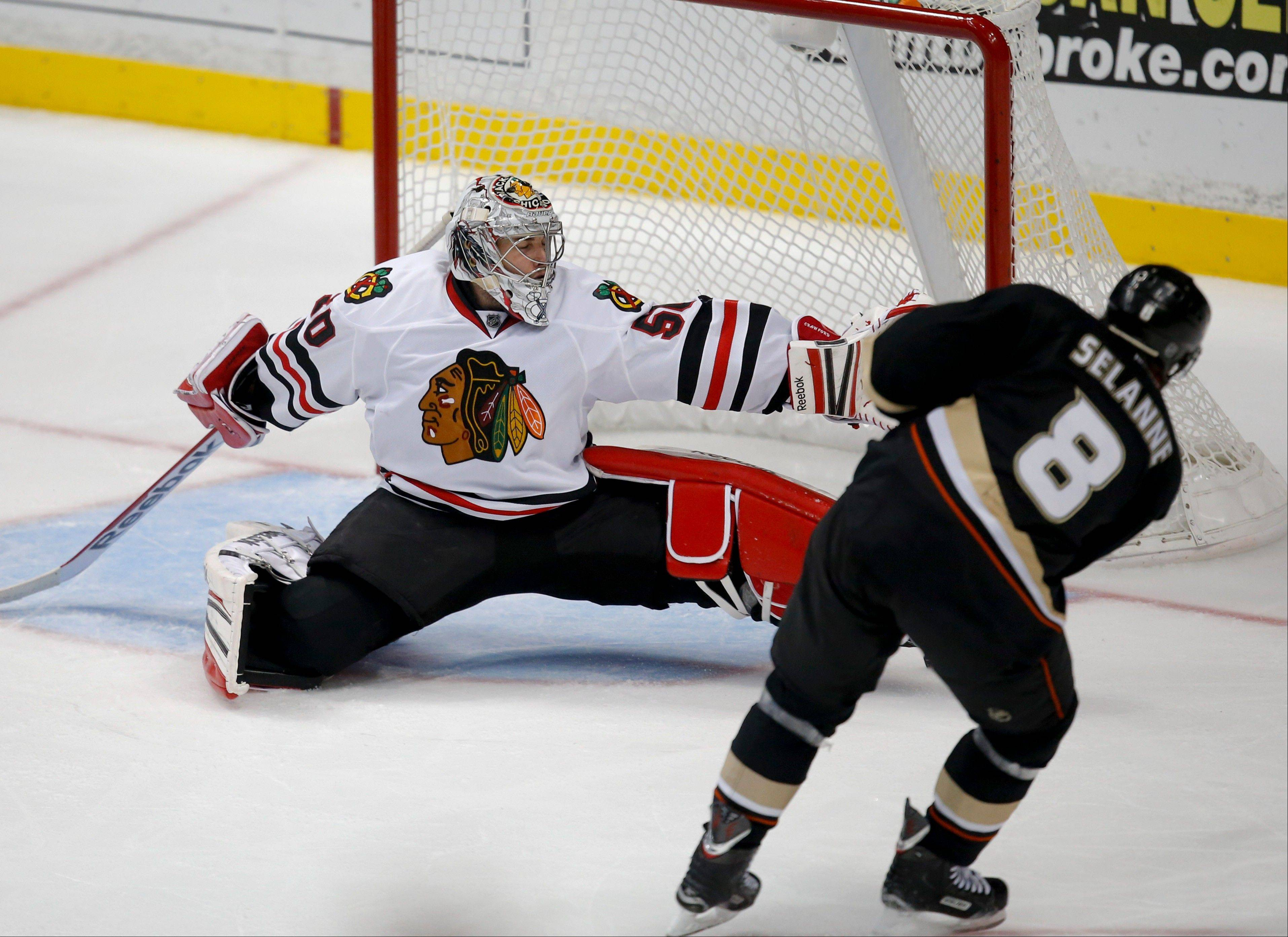 Anaheim Ducks' Teemu Selanne, foreground, of Finland, scores against Chicago Blackhawks goalie Corey Crawford during the third period of an NHL hockey game in Anaheim, Calif., Wednesday, March 20, 2013. The Ducks won 4-2. (AP Photo/Jae C. Hong)