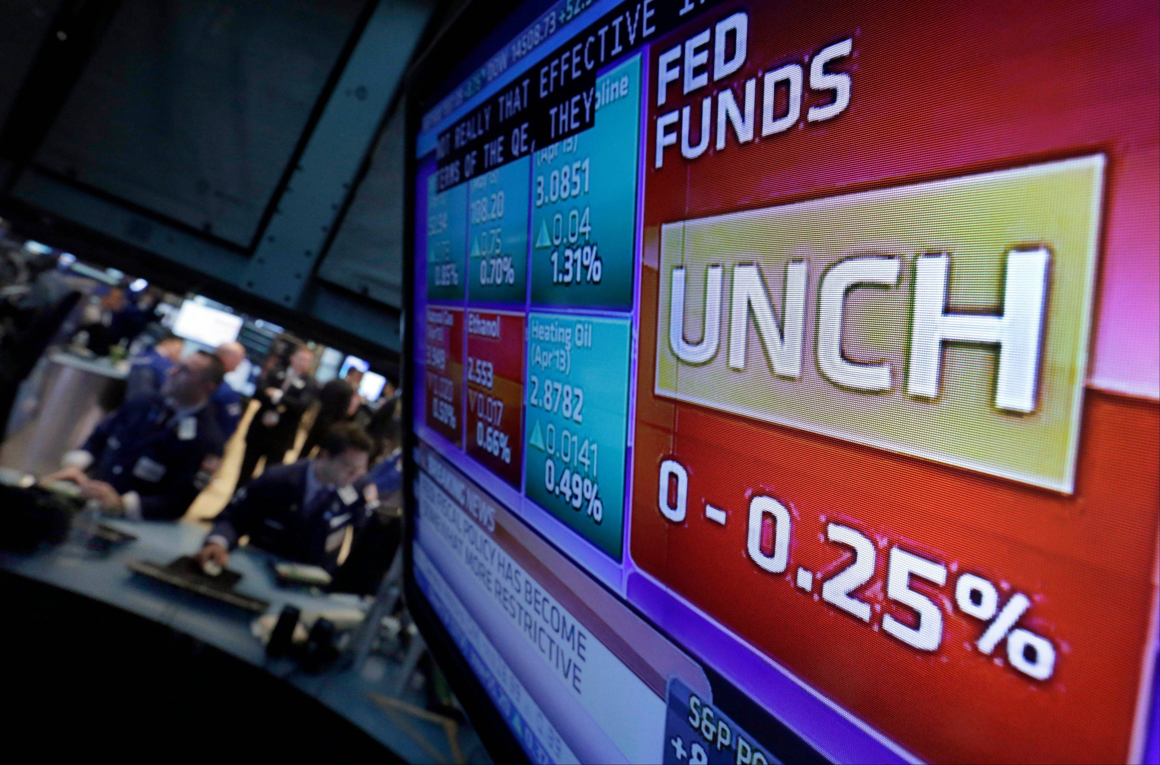 A television screen on the floor of the New York Stock Exchange shows the decision of the Federal Reserve Wednesday to keep short-term rates at record lows at least until unemployment falls to 6.5 percent, as long as the inflation outlook remains mild.