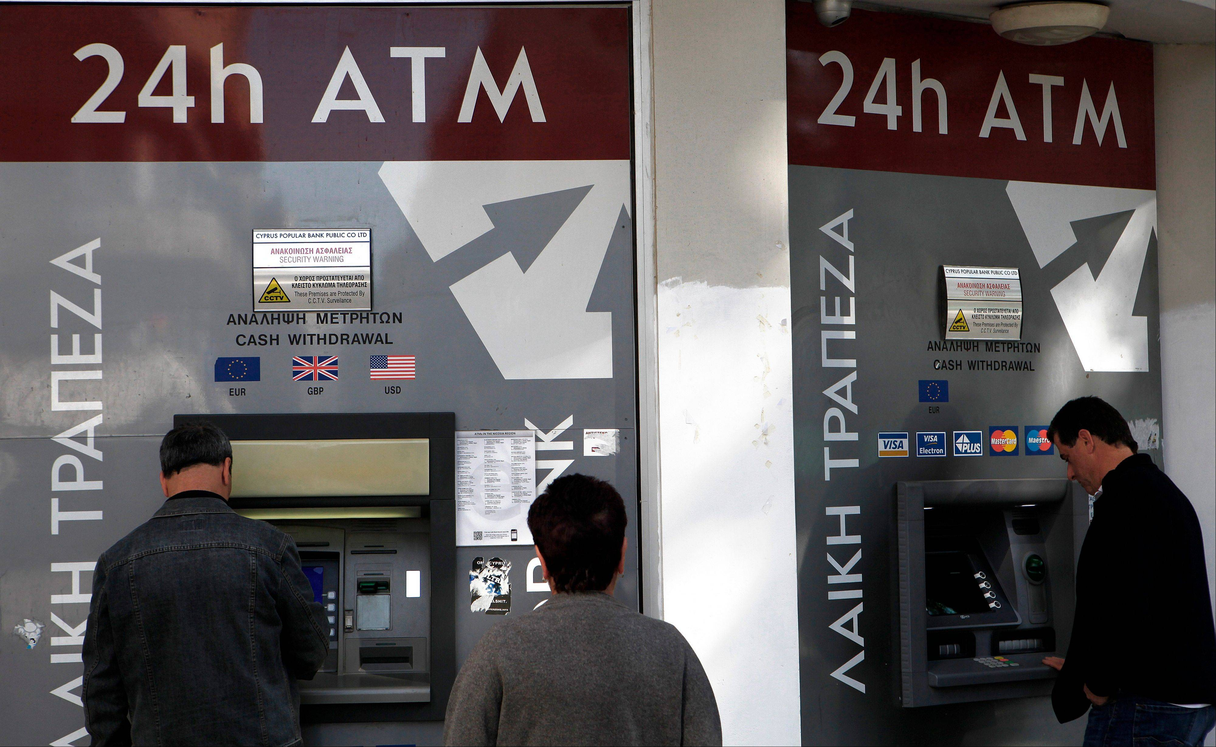 People use the ATMs outside of a closed branch of Laiki Bank in Cyprus Wednesday. Tuesday's decisive rejection of the plan to take a slice of all deposits above $25,888 has left the country's bailout in question. Without the bailout, the Cypriot banking sector would collapse, devastating the country's economy and potentially causing it to leave the euro.