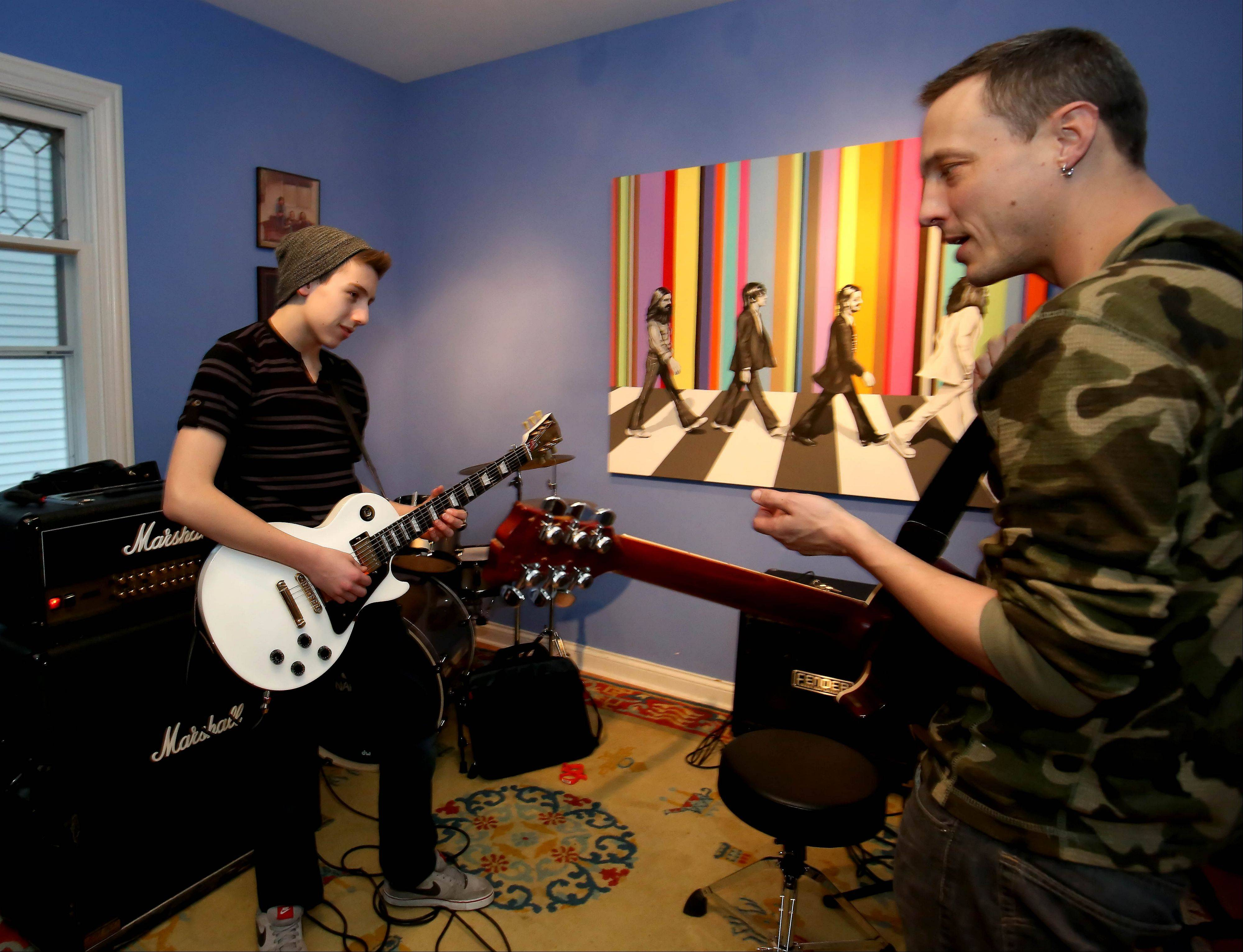 Justin Walsh, 15, of Naperville gets a few tips from instructor Danni Schaper, right, at the School of Rock in Naperville.
