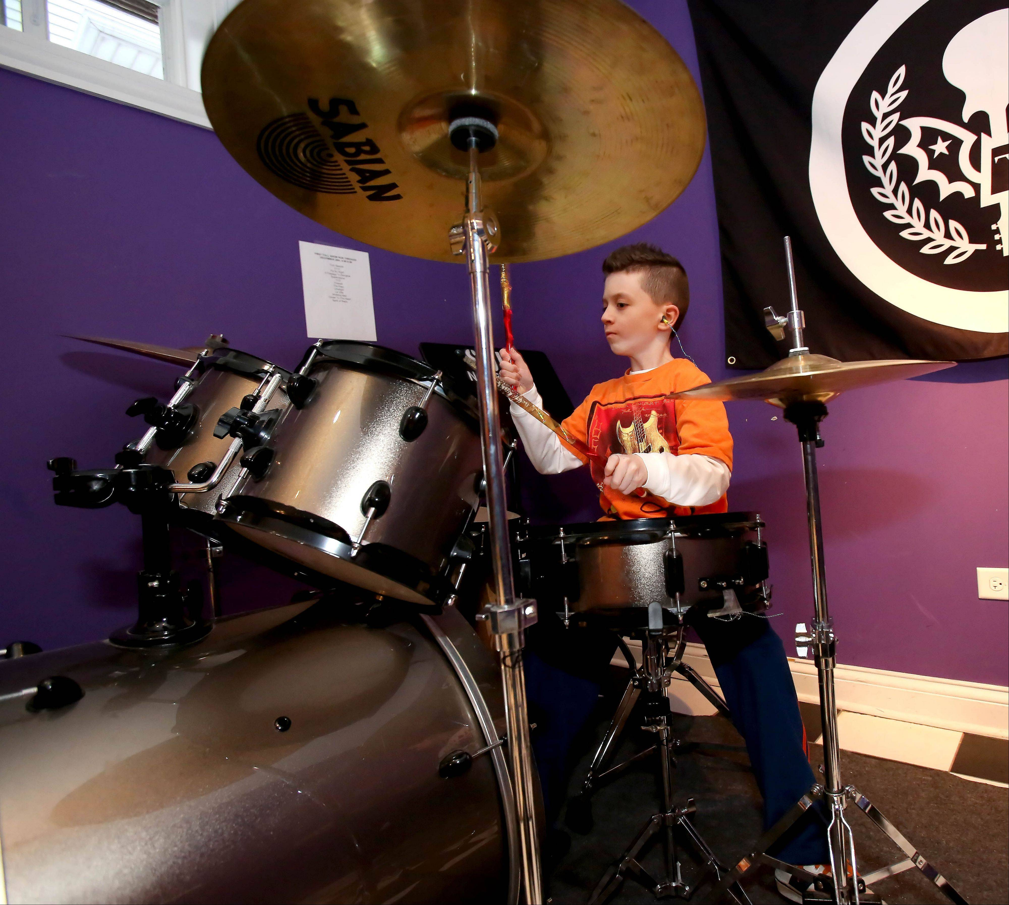 Jacob Deutschman, 8, of Plainfield rehearses a number at the School of Rock in Naperville.