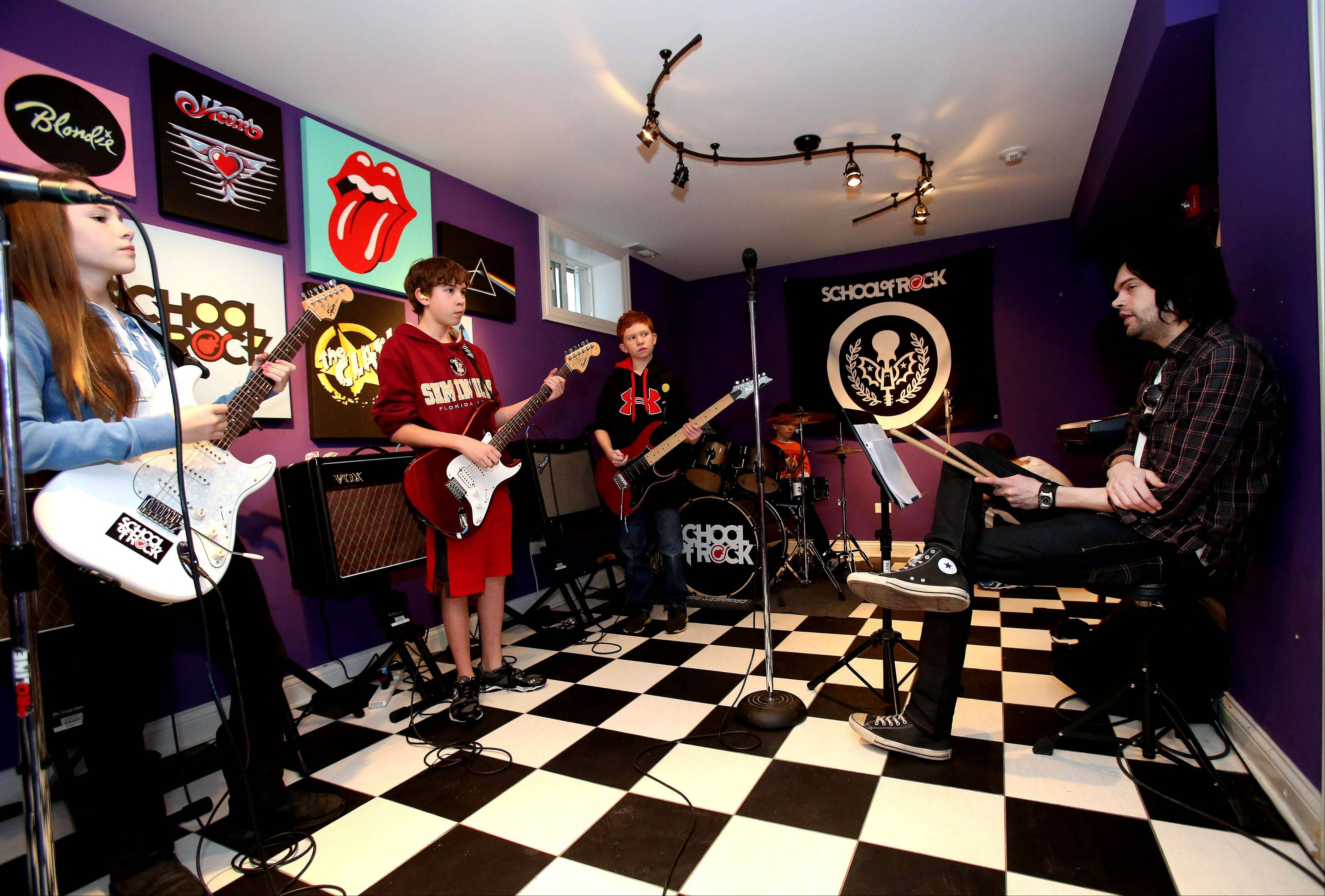 Instructor Adam Krier helps a young band rehearse for a show at the School of Rock in Naperville.