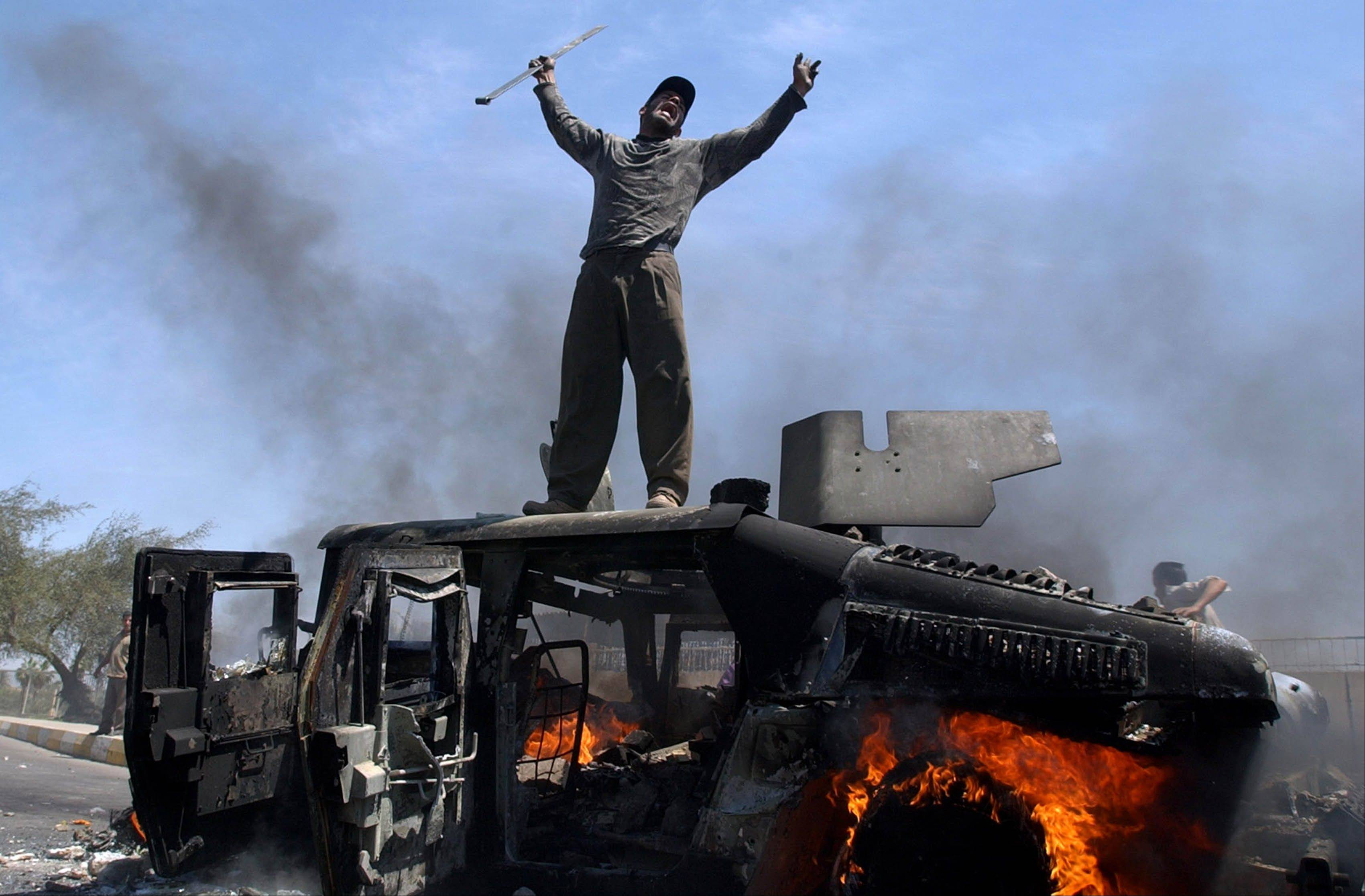 FILE - An Iraqi man celebrates on top of a burning U.S. Army Humvee in the northern part of Baghdad, Iraq on Monday, April 26, 2004.