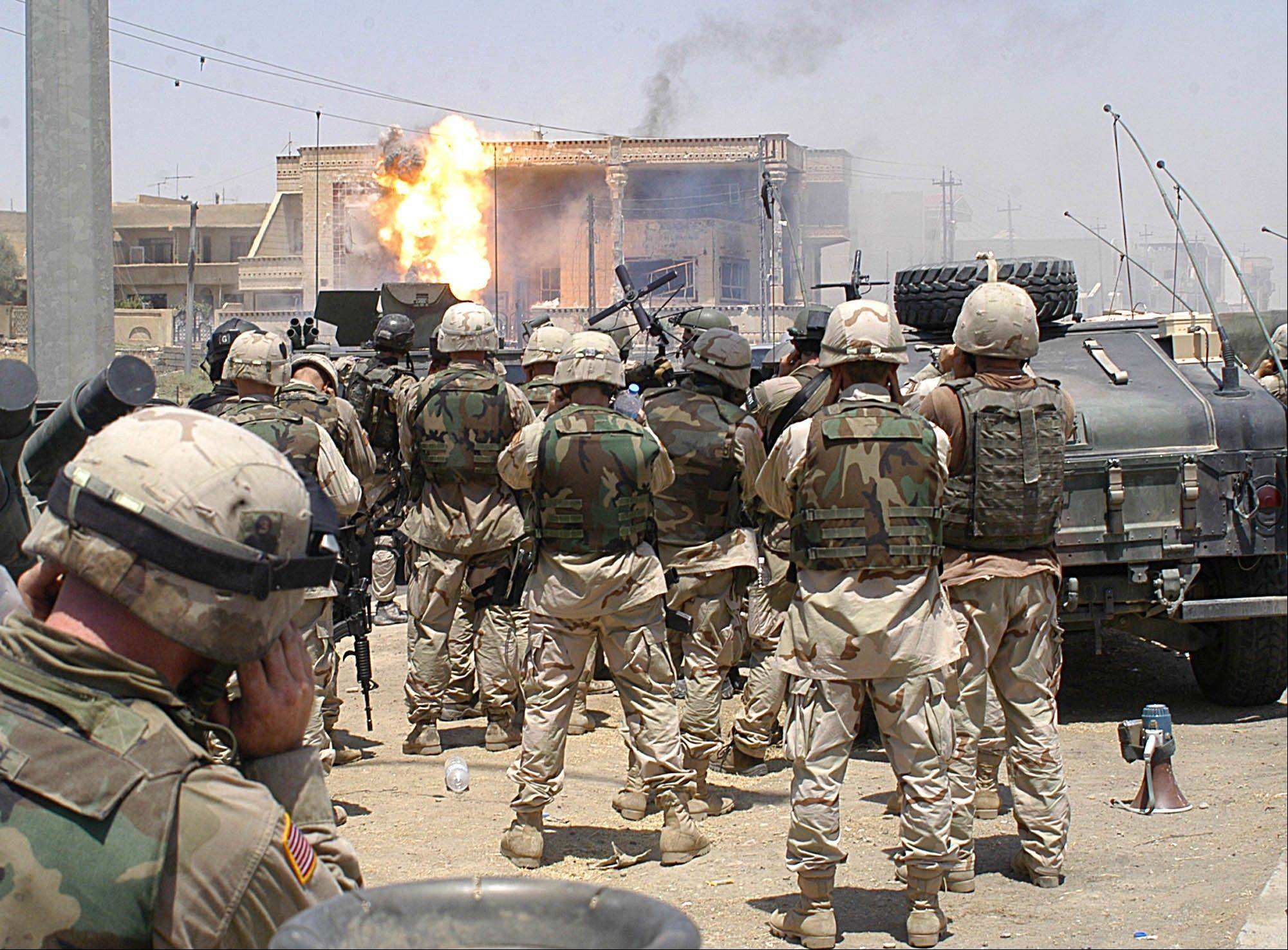 FILE - Flames erupt from a building hit with a TOW missile launched by soldiers of the Army�s 101st Airborne Division (Air Assault) in Mosul, Iraq on July 21, 2003. Saddam Hussein�s sons Qusay and Uday were killed in a gun battle as they resisted efforts by coalition forces to apprehend and detain them.