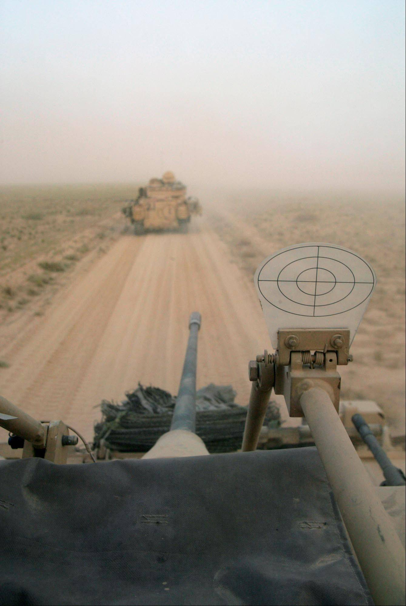 FILE - U.S. Army Bradley fighting vehicles travel in a convoy through the dust carrying infantrymen just after crossing the border into southern Iraq on Friday, March 21, 2003.