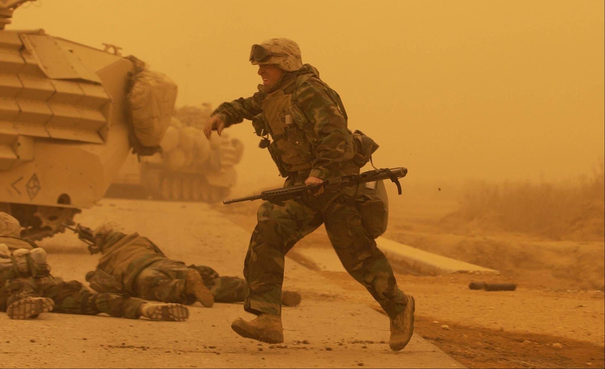 FILE - U.S. Marines with 3rd Battalion, 7th Marines, 1st Marine Division, take cover after a mortar attack during a sandstorm on a road south of Baghdad, Iraq on Wednesday, March 26, 2003.