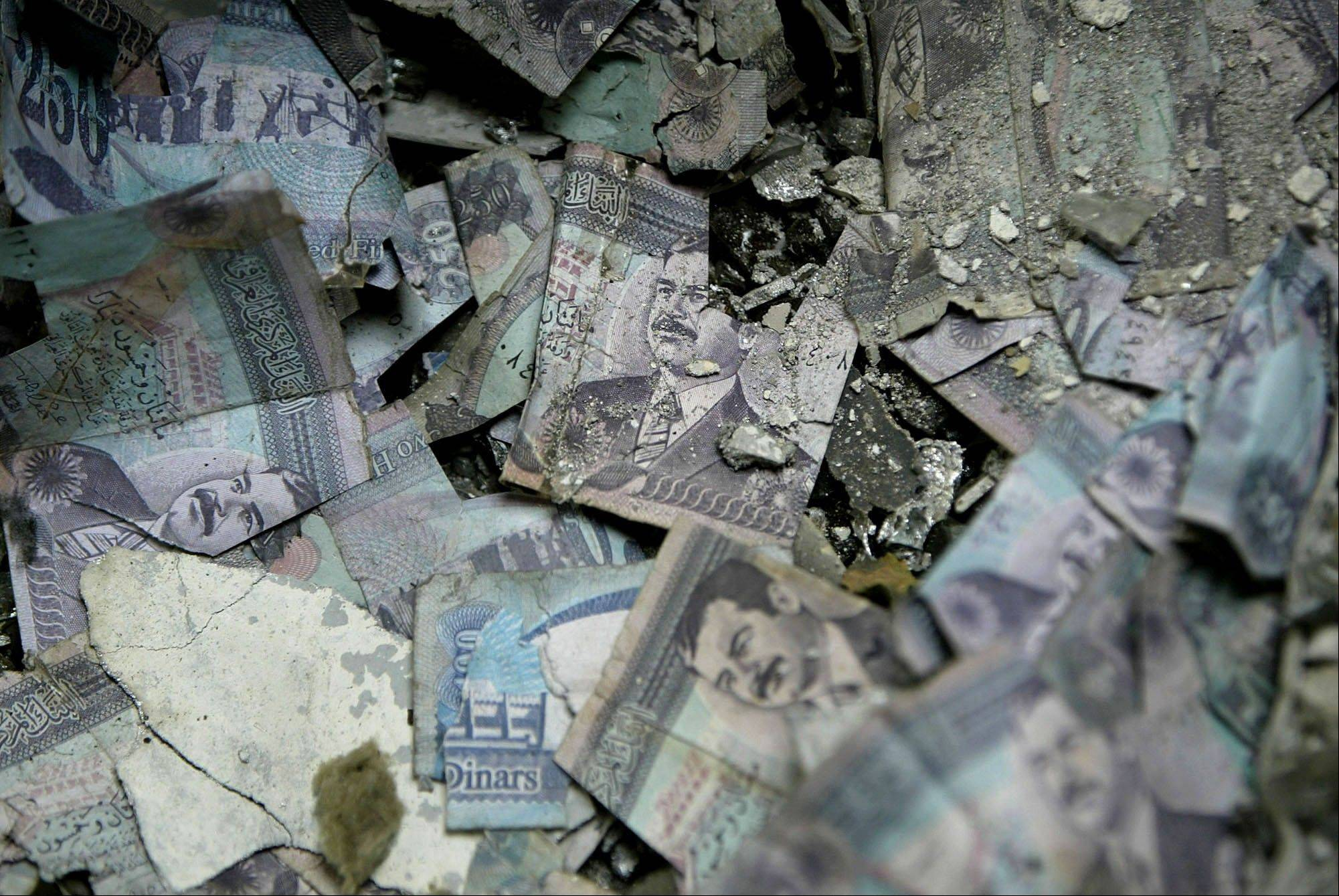 FILE - Piles of torn and burned Iraqi currency bearing the portrait of Saddam Hussein lie in ashes on the floor of the burned Baghdad Central Bank on Friday, April 18, 2003.