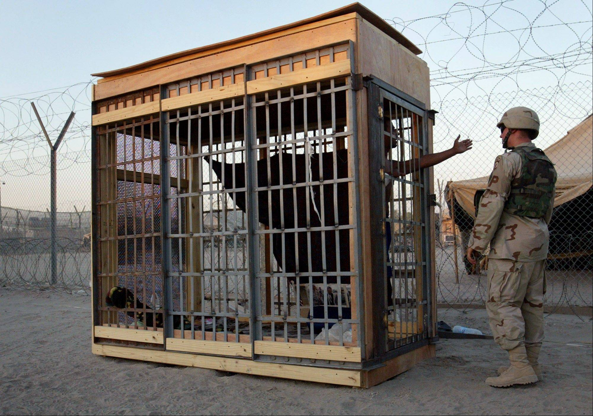 FILE - A detainee in an outdoor solitary confinement cell talks with a military policeman at the Abu Ghraib prison on the outskirts of Baghdad, Iraq on Tuesday, June 22, 2004.