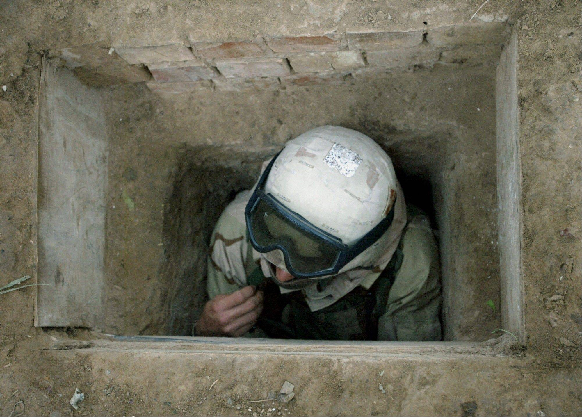 FILE - A U.S. soldier demonstrates access to a shaft used by former Iraqi leader Saddam Hussein before he was captured two days earlier, on a farm near Tikrit, northern Iraq on Monday, Dec. 15, 2003.