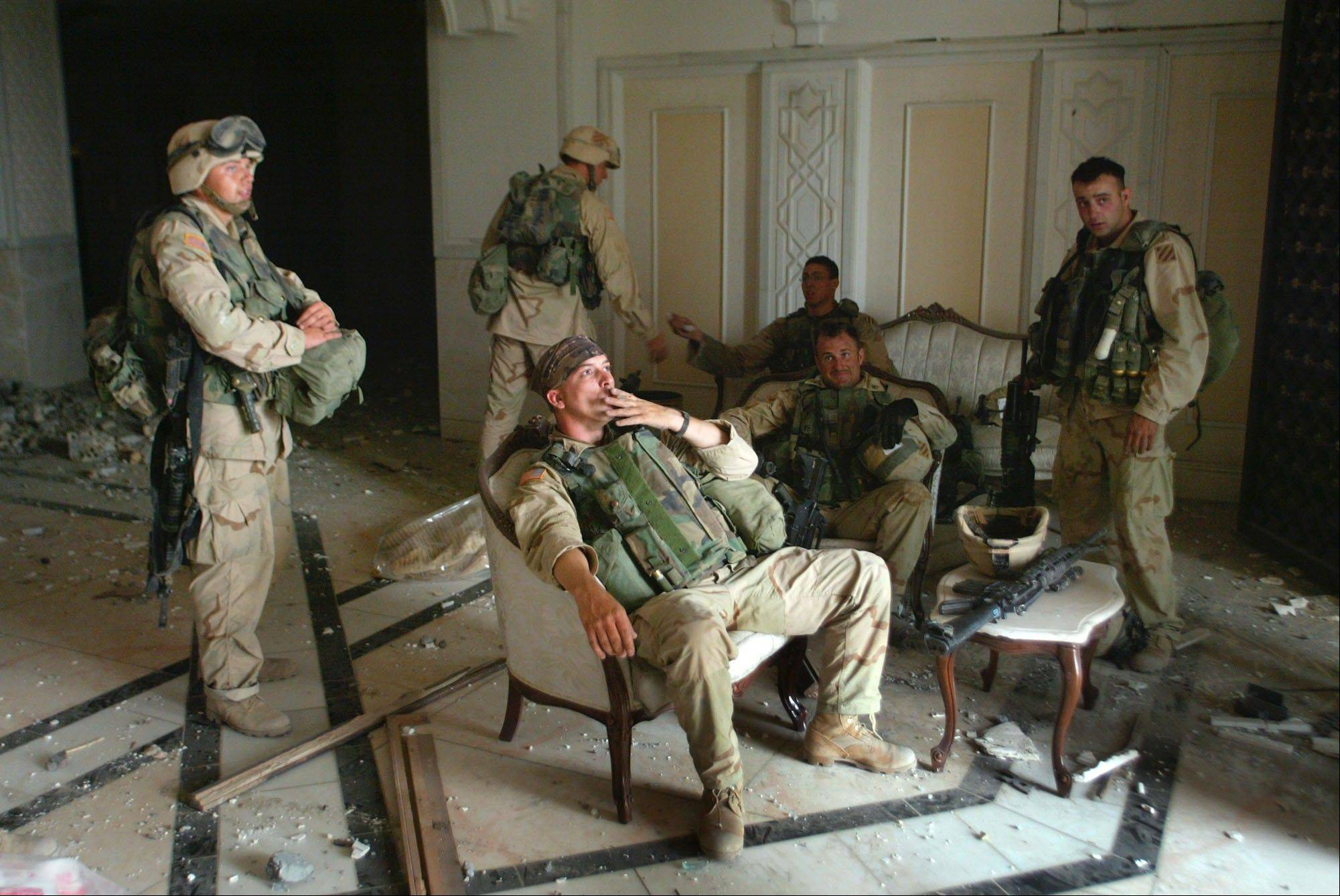 FILE - U.S. Army Stf. Sgt. Chad Touchett, center, relaxes with comrades from A Company, 3rd Battalion, 7th Infantry Regiment, after a search of one of Saddam Hussein's bomb-damaged palaces in Baghdad on Monday, April 7, 2003.