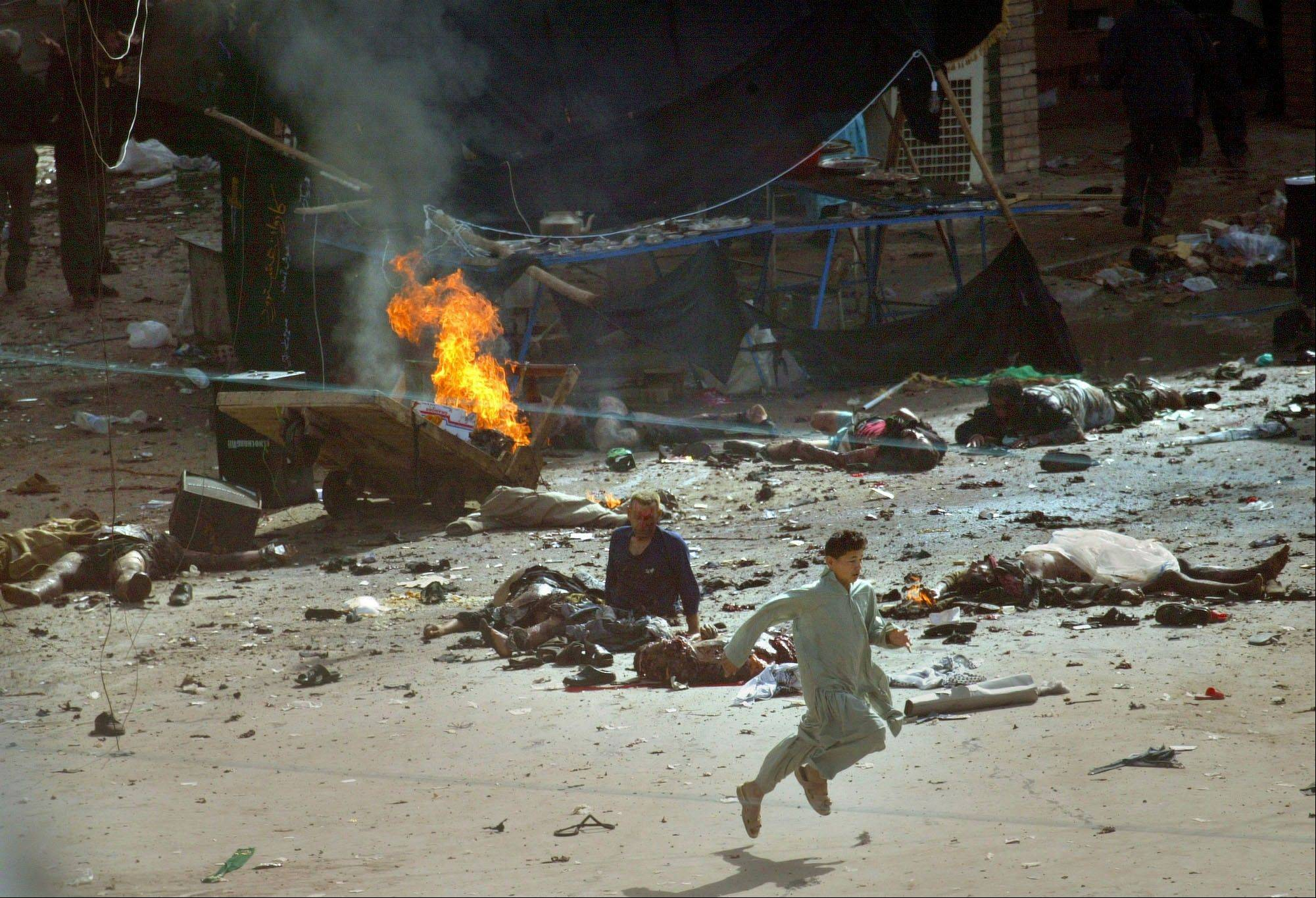 FILE - Moments after the explosions, a youth runs past the victims and burning debris at the site of several bomb blasts in densely-occupied areas during the holy day of Ashoura, a Shiite festival, in the holy city of Karbala, Iraq on Tuesday, March 2, 2004.