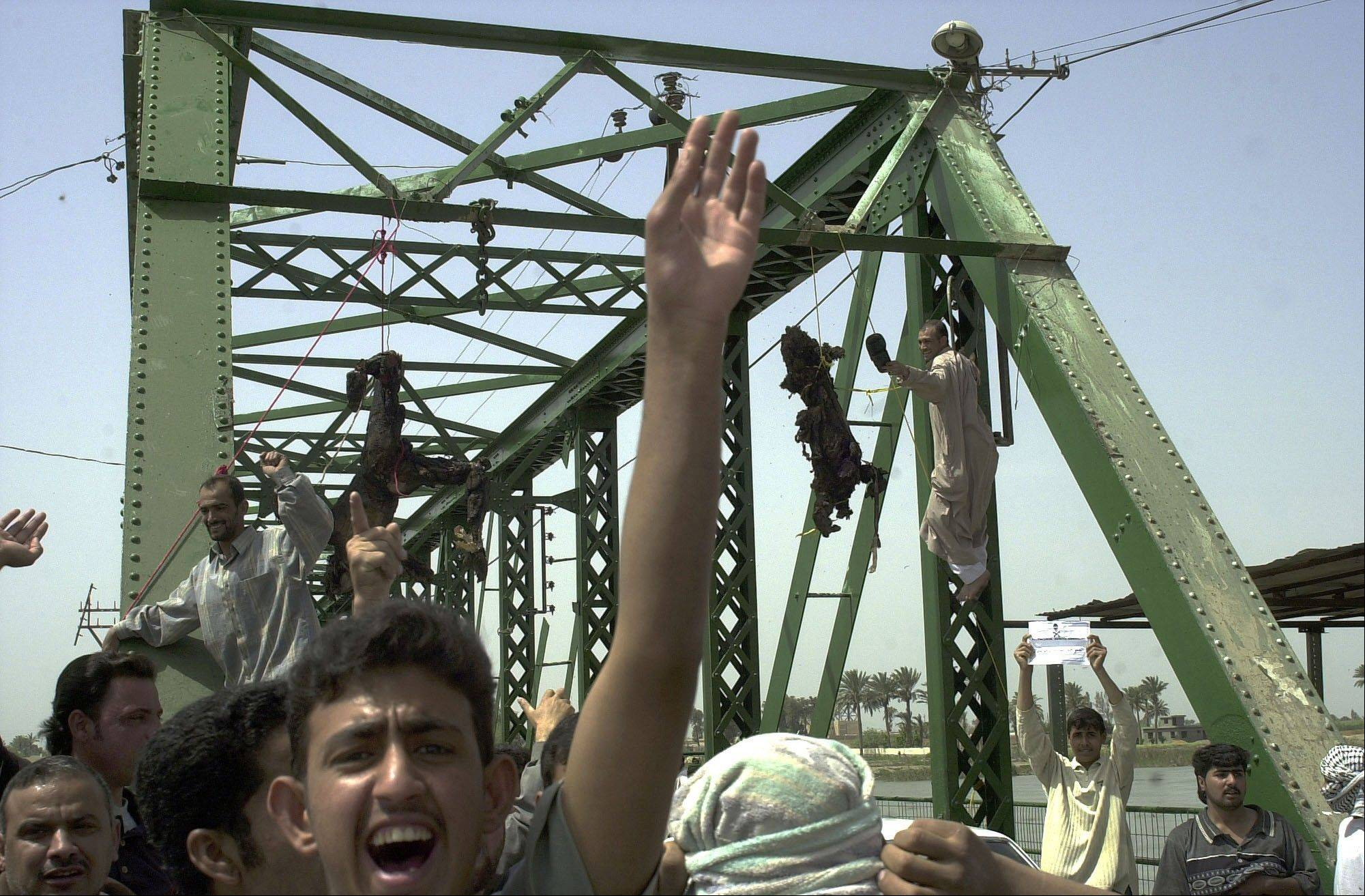 FILE - Demonstrators chant anti-American slogans as charred and mutilated bodies of U.S. contractors hang from a bridge over the Euphrates River in Fallujah, west of Baghdad, on March 31, 2004.