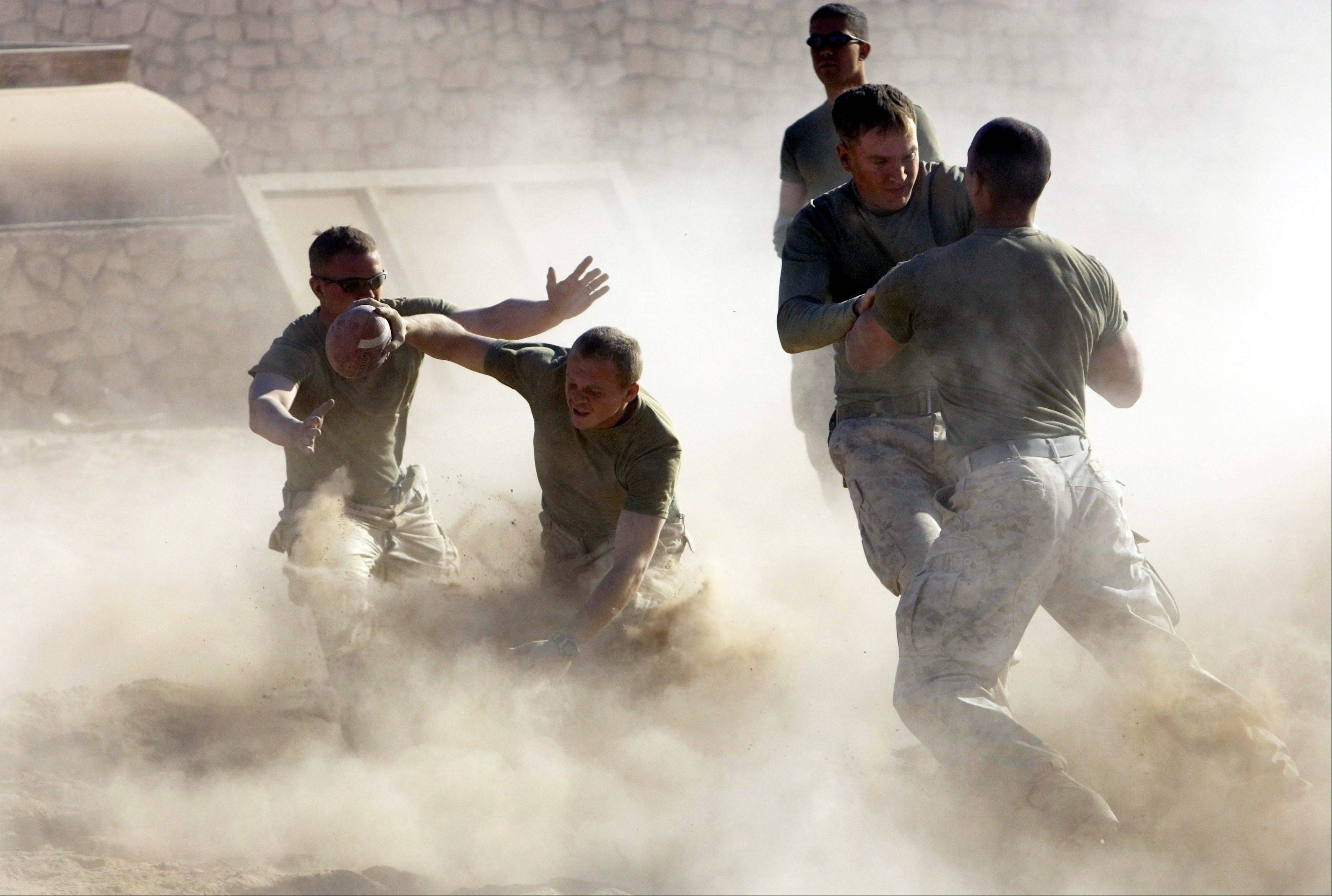 FILE - U.S. Marines play football in Karabilah, Iraq, near the Syrian border, on Thursday, Nov. 24, 2005 during Thanksgiving celebrations.