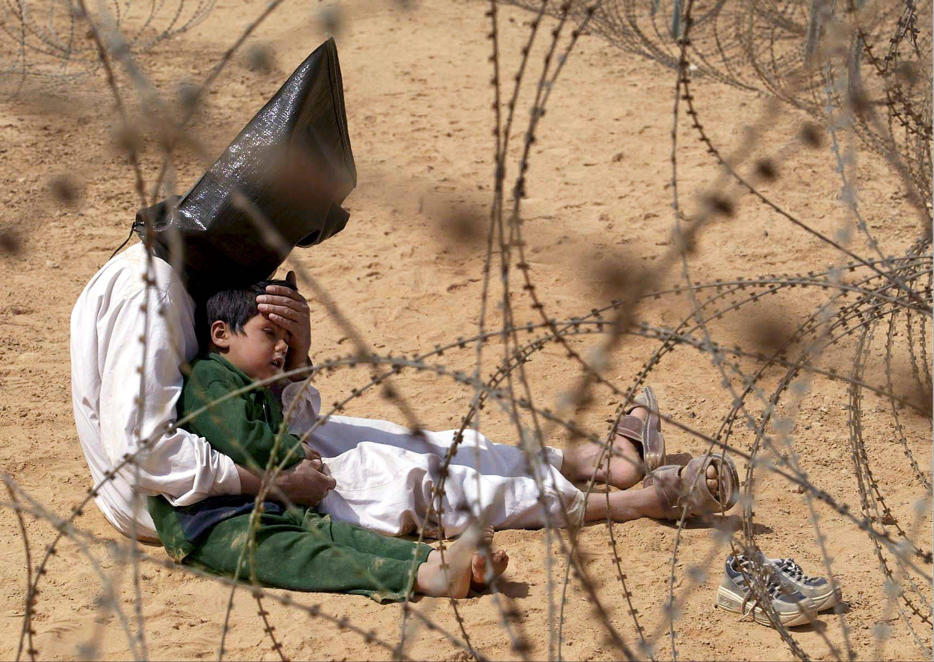 FILE - An Iraqi prisoner of war comforts his 4-year-old son at a regrouping center for POWs captured by the U.S. Army 101st Airborne Division near Najaf, Iraq on March 31, 2003.