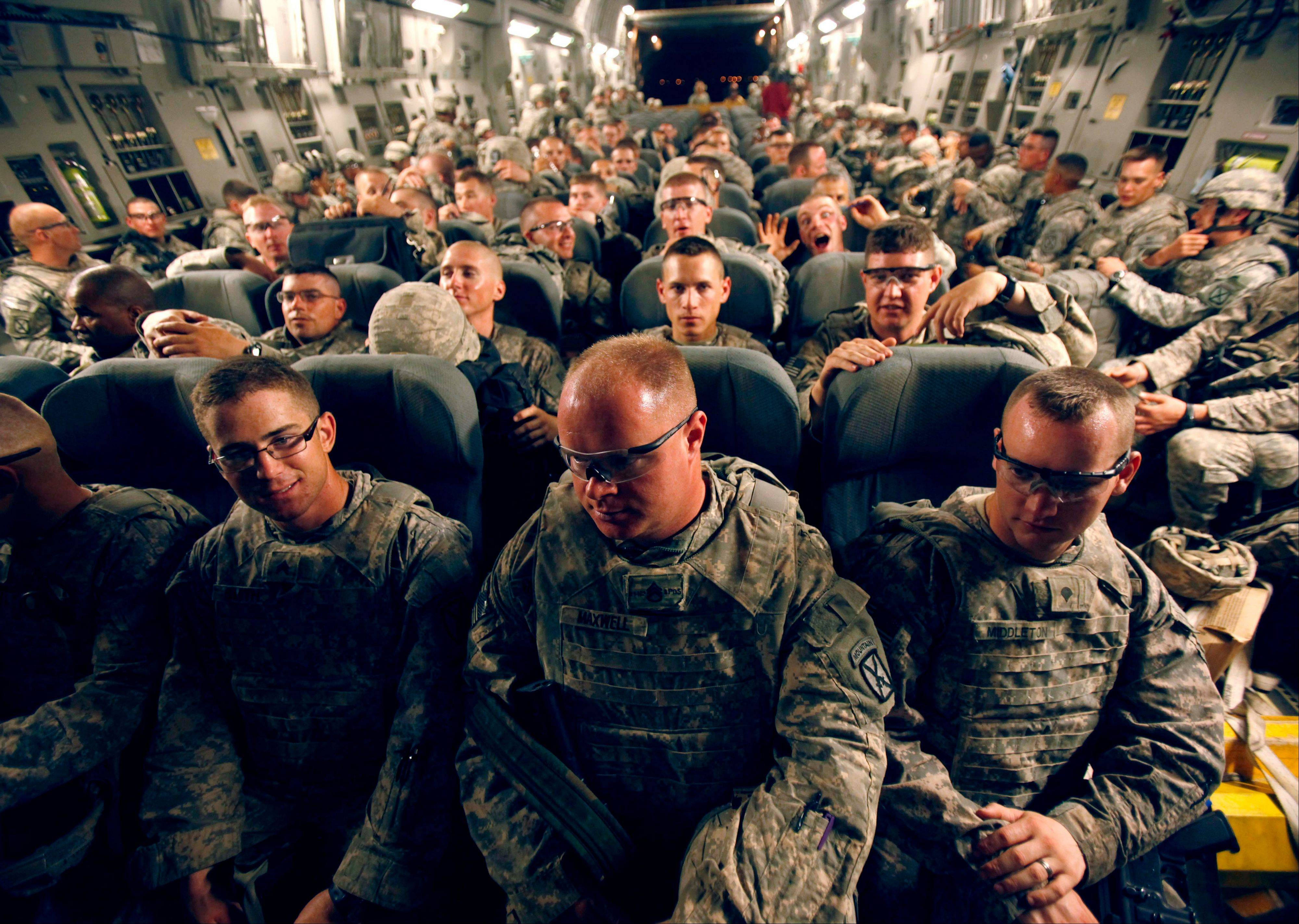 FILE - U.S. Army soldiers from 2nd Brigade, 10th Mountain Division are seated aboard a C-17 aircraft at Baghdad International Airport en route back to the United States on Tuesday, July 13, 2010.