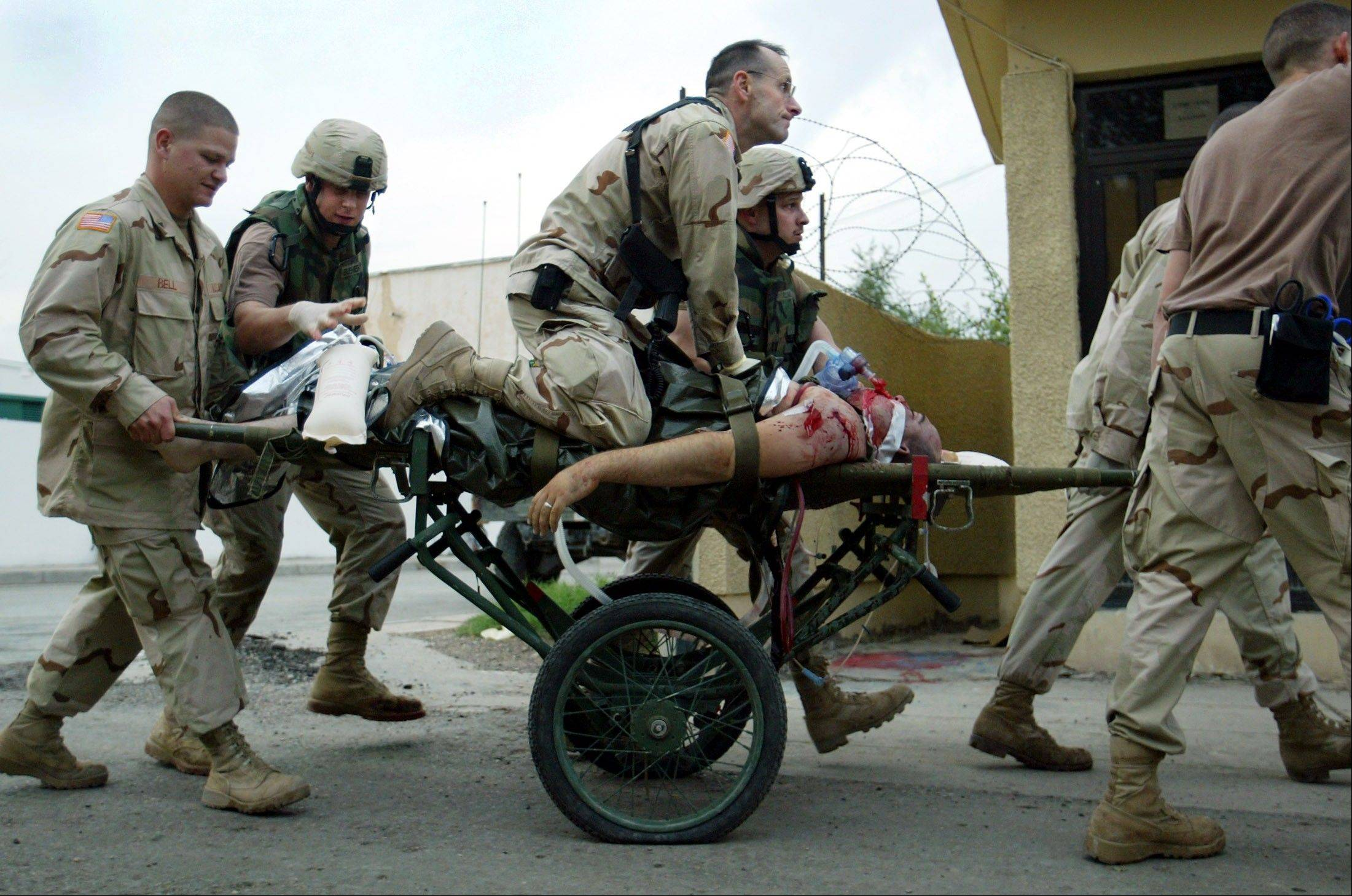 FILE - U.S. Army Nurse supervisor Patrick McAndrew tries to save the life of an American soldier by giving him CPR on a stretcher as he arrived at a military hospital in Baghdad, Iraq on Tuesday, Nov. 9, 2004. The soldier was fatally wounded in a Baghdad firefight with insurgents.