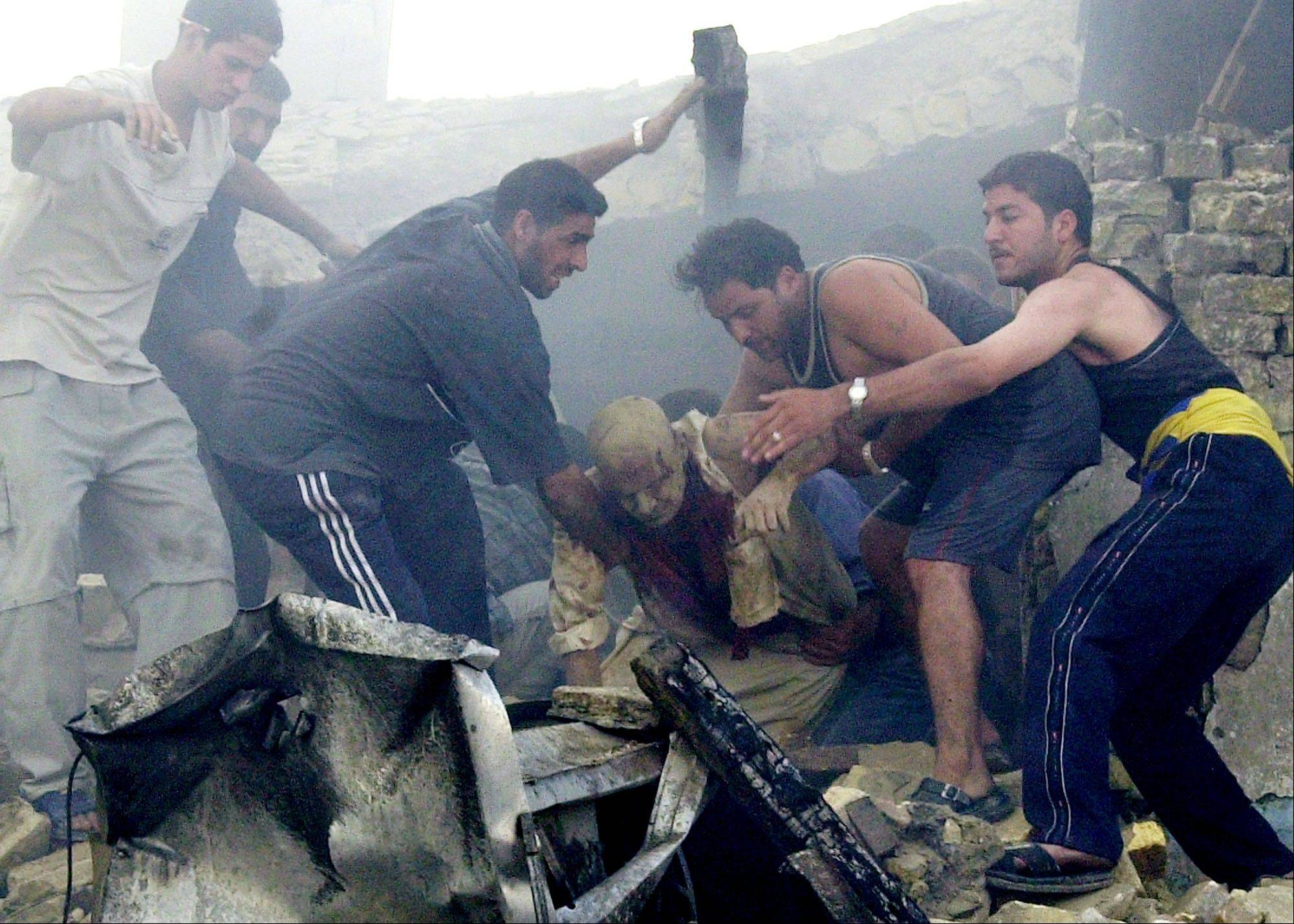 FILE - People carry an injured man from a damaged building after a car bomb exploded in central Baghdad, Iraq on Monday, June 14, 2004, killing at least 10 people, including three foreigners working to rebuild Iraq's power plants.
