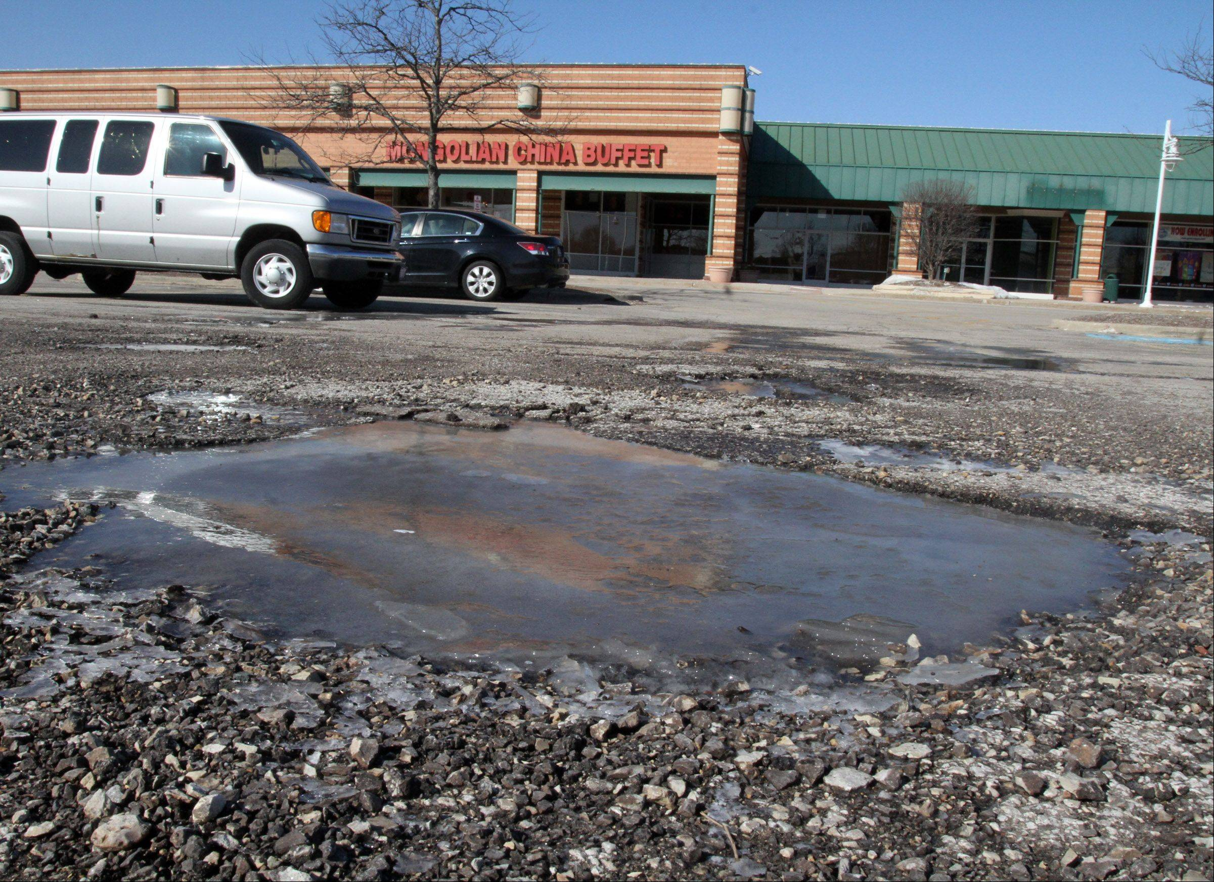 This is a pothole filled with frozen water in the parking lot at Buffalo Grove Town Center at Lake-Cook Road and McHenry Road in Buffalo Grove on Wednesday, March 20.