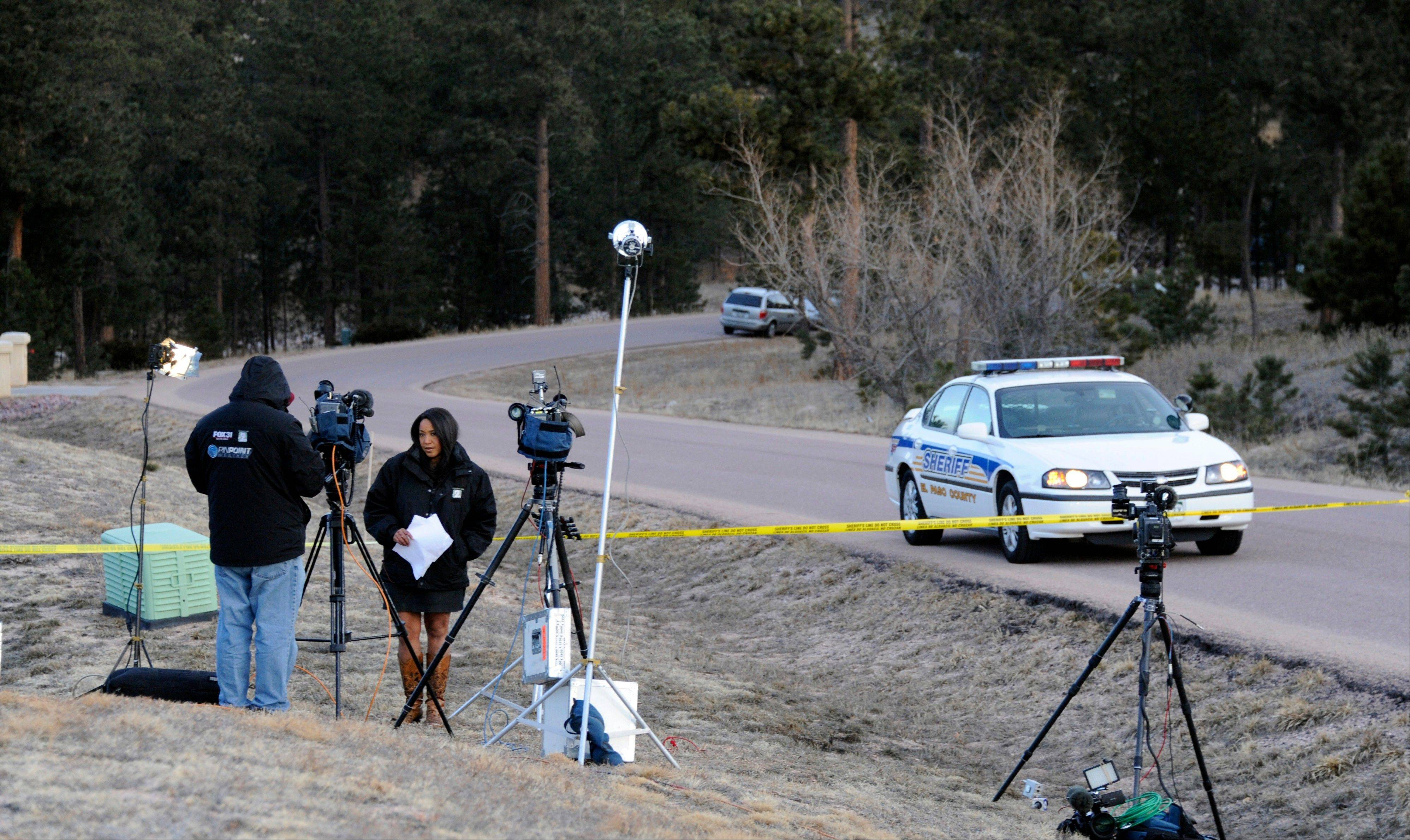 Journalists wait to report Wednesday morning, March 20, 2013, at the scene of an overnight shooting in Monument, Colo., that left Colorado Department of Corrections Director Tom Clements dead at his home. Clements was shot and killed Tuesday evening when he answered the front door of his house, and police are searching for the gunman.