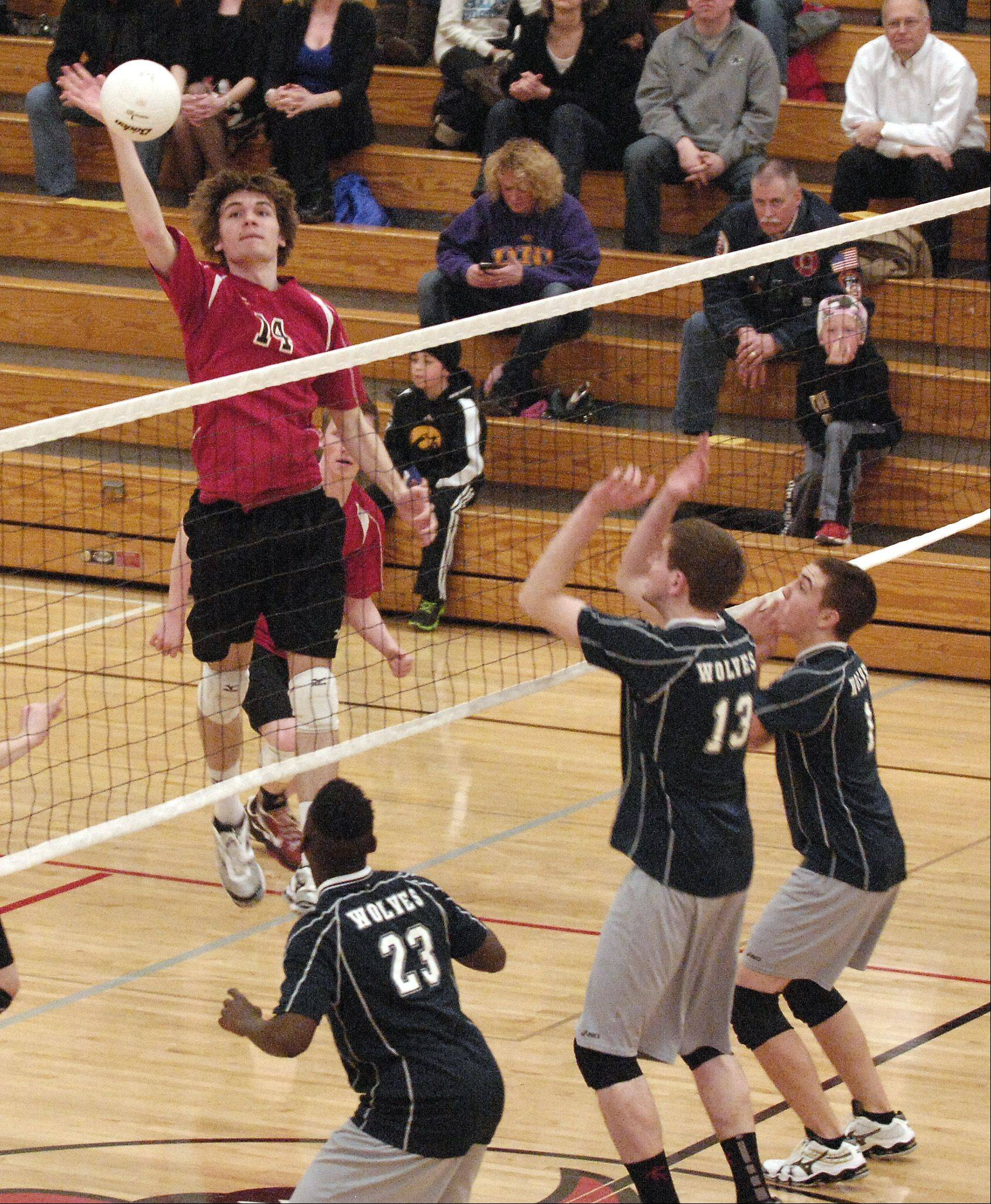 Garrett Metzger of Benet Academy fires one past Oswego East during thier win during boys varsity volleyball, Wednesday at home.