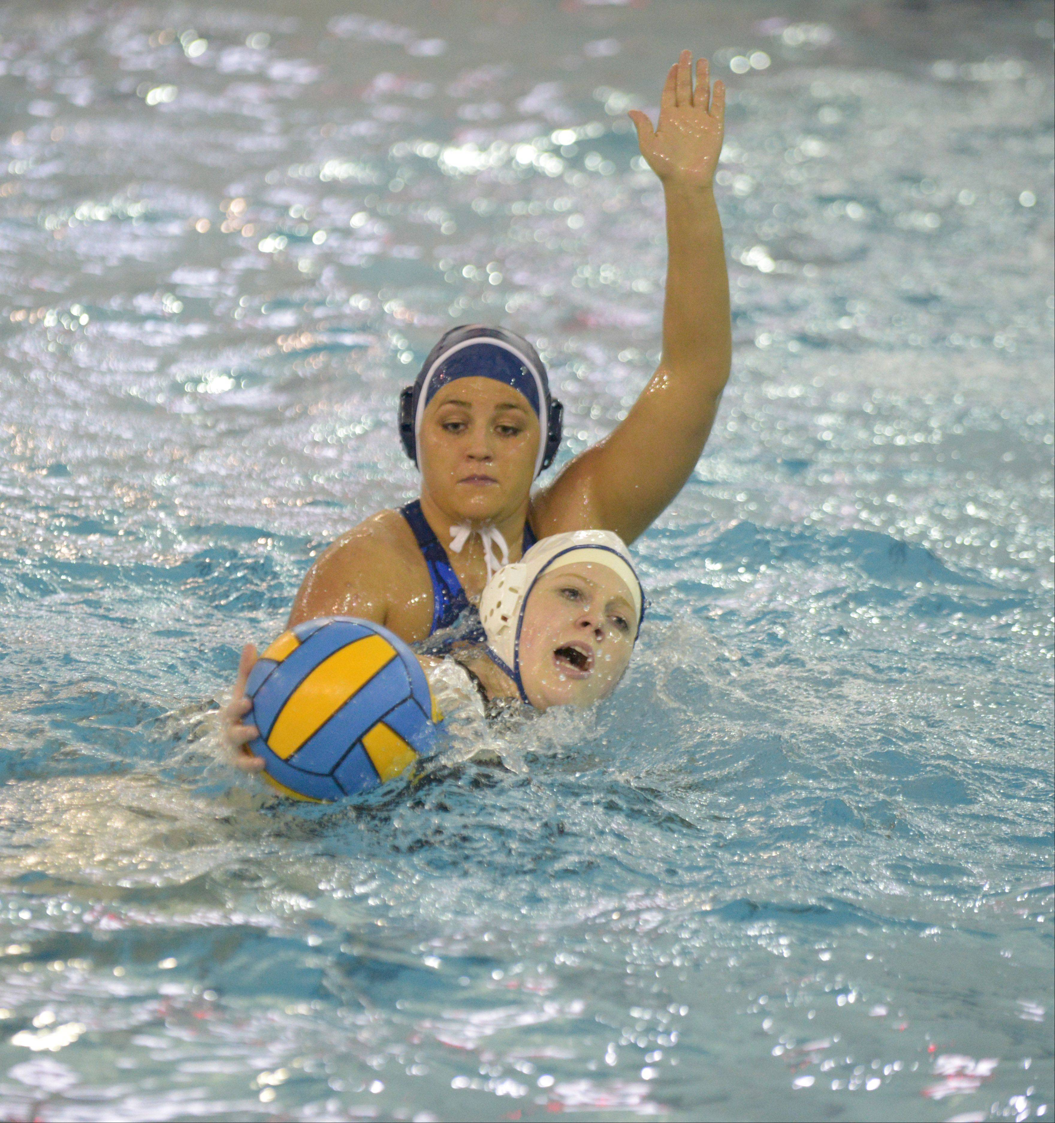Sarah Stern of St. Charles North,left, moves the ball while Taylor Stoner of Naperville North attempts to block during the St. Charles North at Naperville North girls water polo game Wednesday.