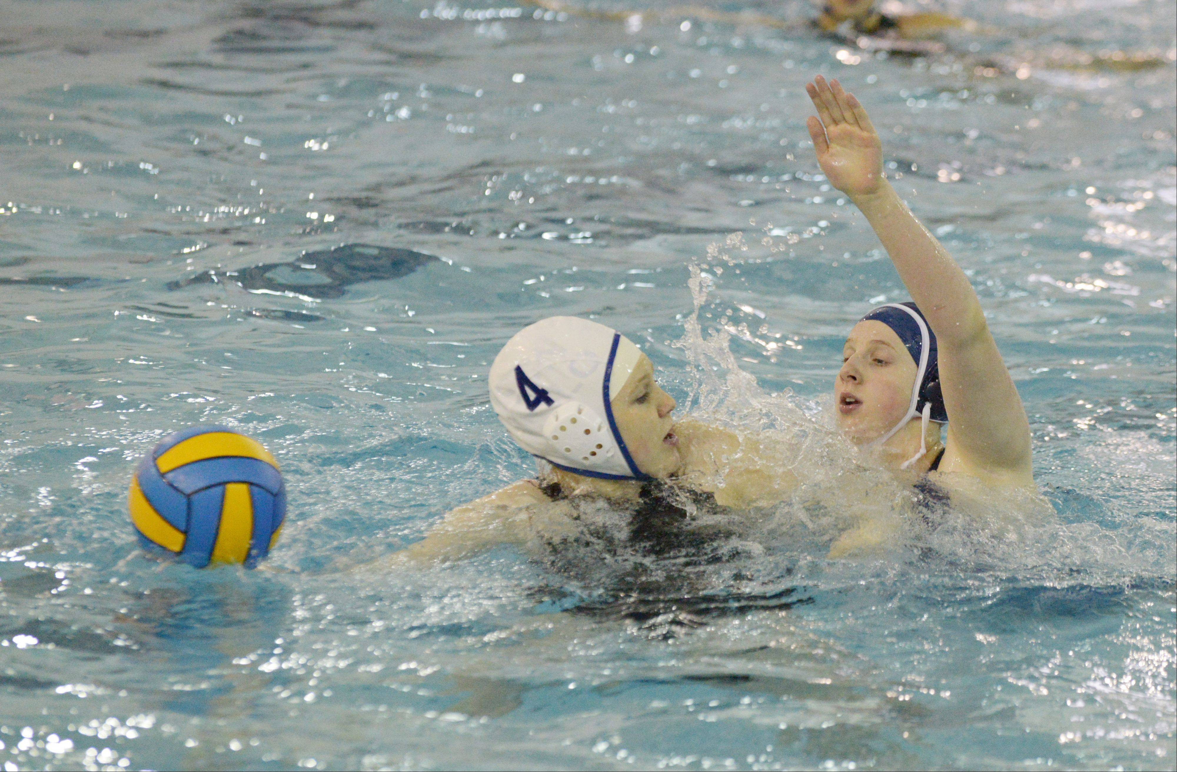 Sarah Stern of St. Charles North looks to pass the ball over Caitlin Holzer of Naperville North. This took place during the St. Charles North at Naperville North girls water polo game Wednesday.