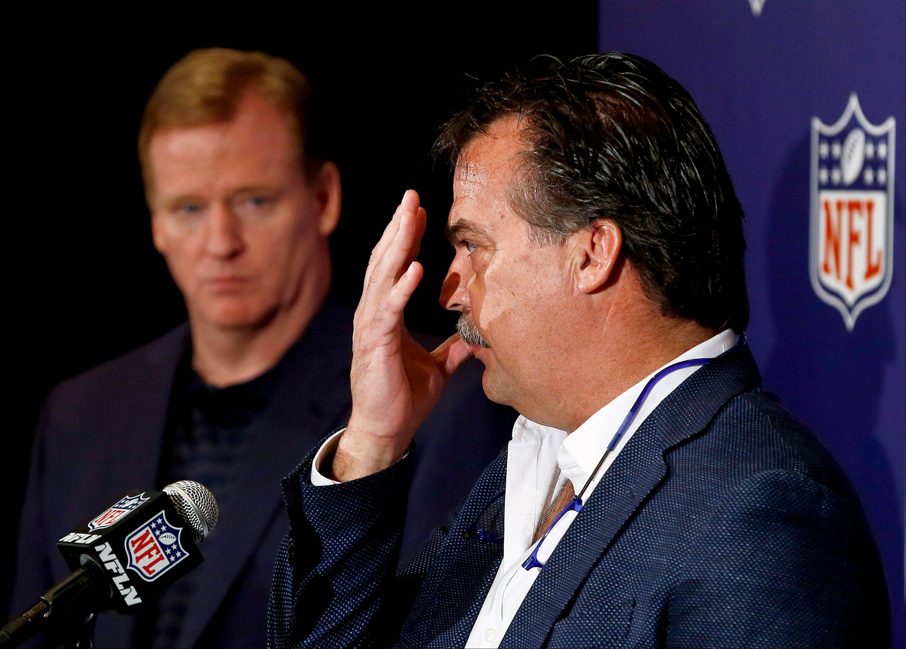 St. Louis Rams head coach and co-chairman of the NFL competition committee Jeff Fisher, right, speaks as NFL Commission Roger Goodell, left, watches at the annual NFL football meetings at the Arizona Biltmore, Wednesday, March 20, 2013, in Phoenix. Fisher explained a new rule passed by NFL owners barring ball carriers from using the crown of their helmets to make forcible contact with a defender in the open field.