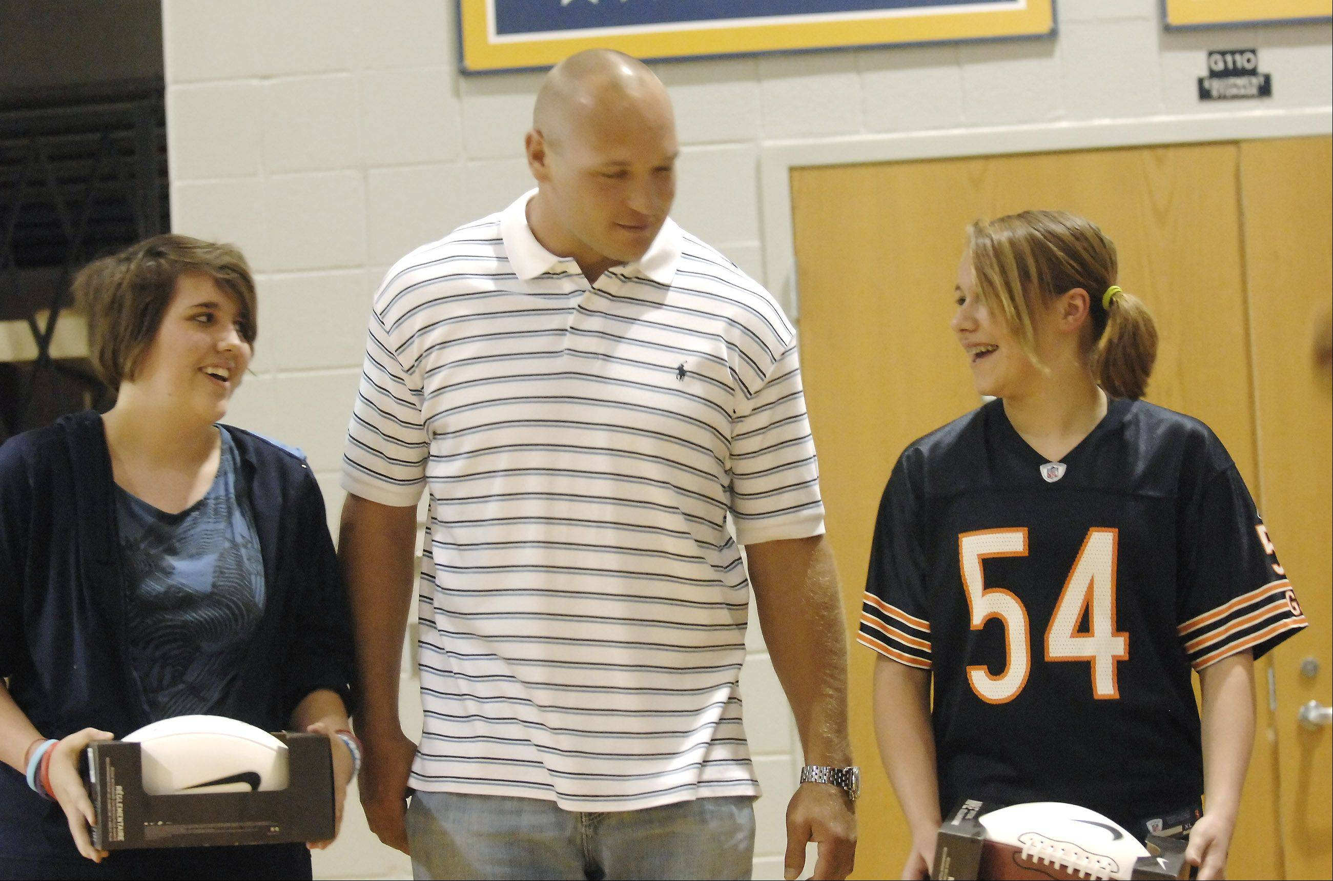 Top fundraisers Katie Baker, left, and Rehann Schleiter, right, received footballs from Brian Urlacher, center. Chicago Bears' Brian Urlacher made a surprise visit to Granger Middle School in Aurora to pass out awards to winners in the school's Football For The Heart program and medals to Special Olympians from competition earlier in the month.