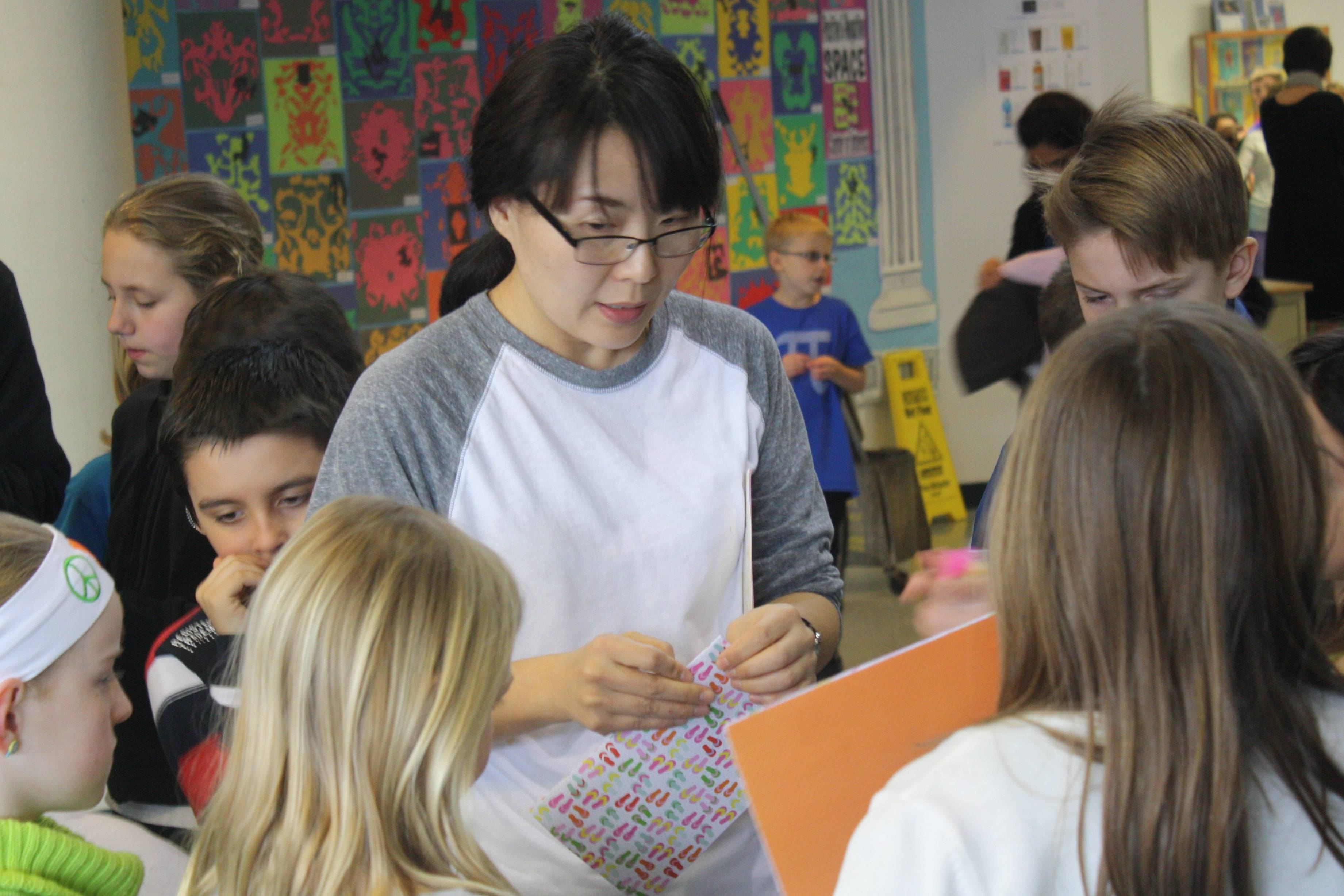 A student from Harper College's Intensive English program shows elementary school students how to make the Korean game Ddakji.