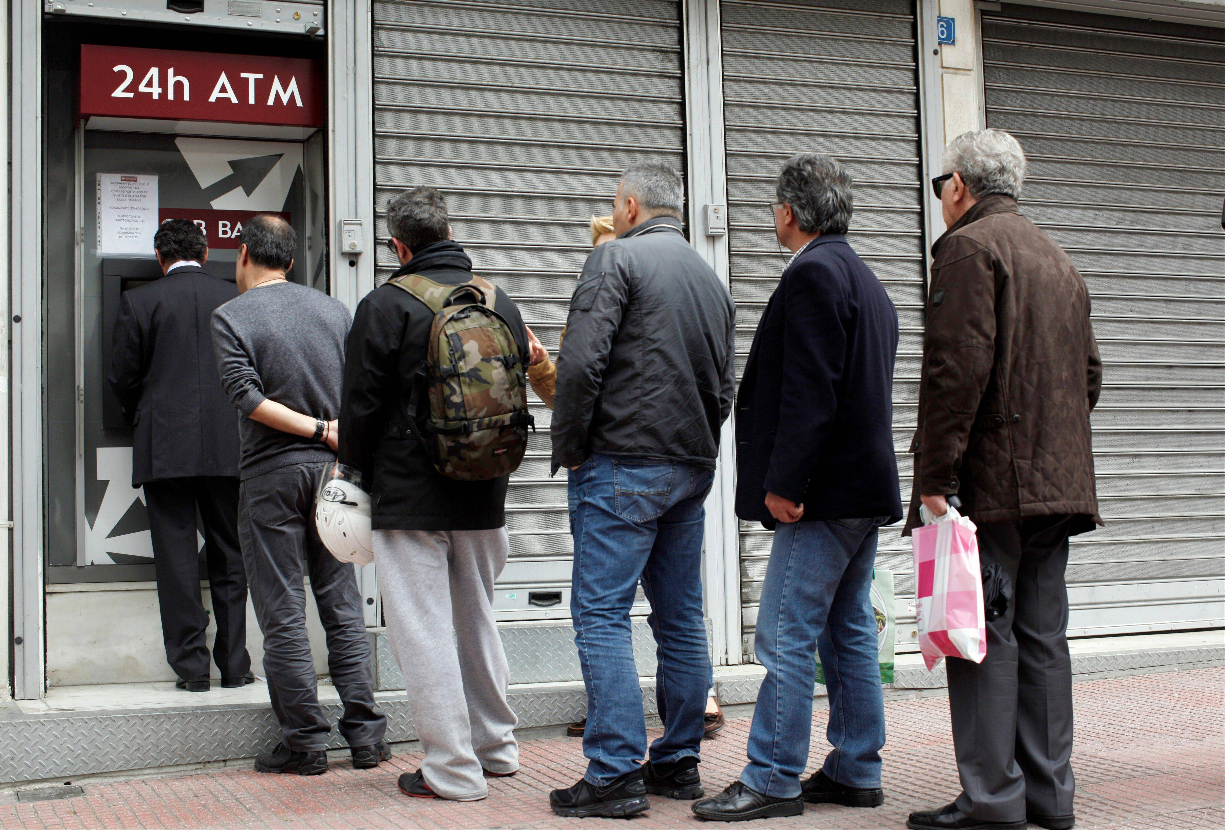 Customers wait to withdraw money from an ATM outside a closed branch of CPB Bank, part of Cyprus Popular Bank Pcl, also known as Laiki Bank in Athens, Greece, on Thursday, March 21, 2013. Branches of Cypriot lenders in Greece will remain closed on March 21 and March 22 following a decision of the Central Bank of Cyprus, Greece's Finance Ministry said in an emailed statement today.