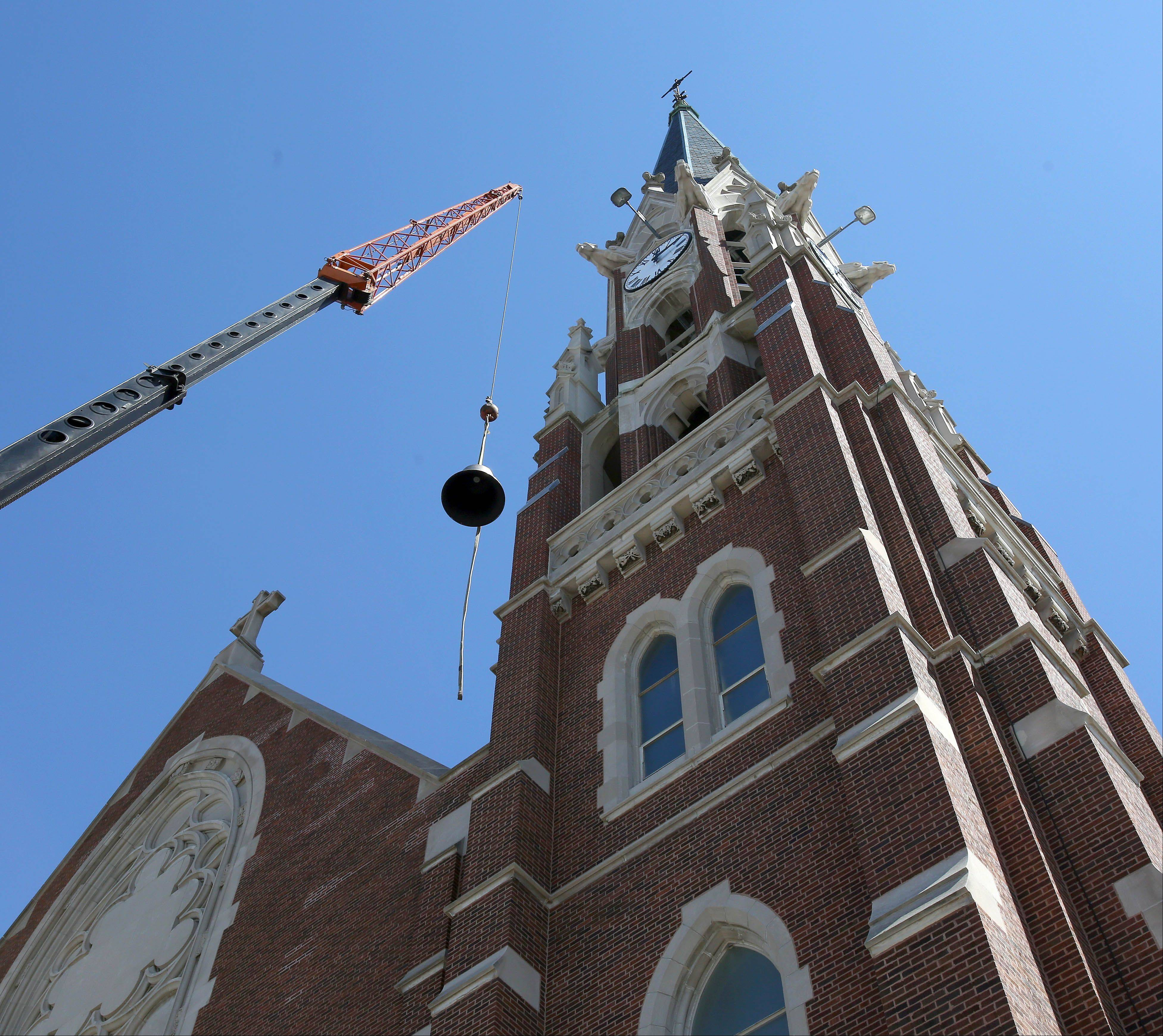 A bell is lifted into the tower Thursday at Naperville's Ss. Peter and Paul Catholic Church near downtown. The church's new bells will ring for the first time over Easter weekend.