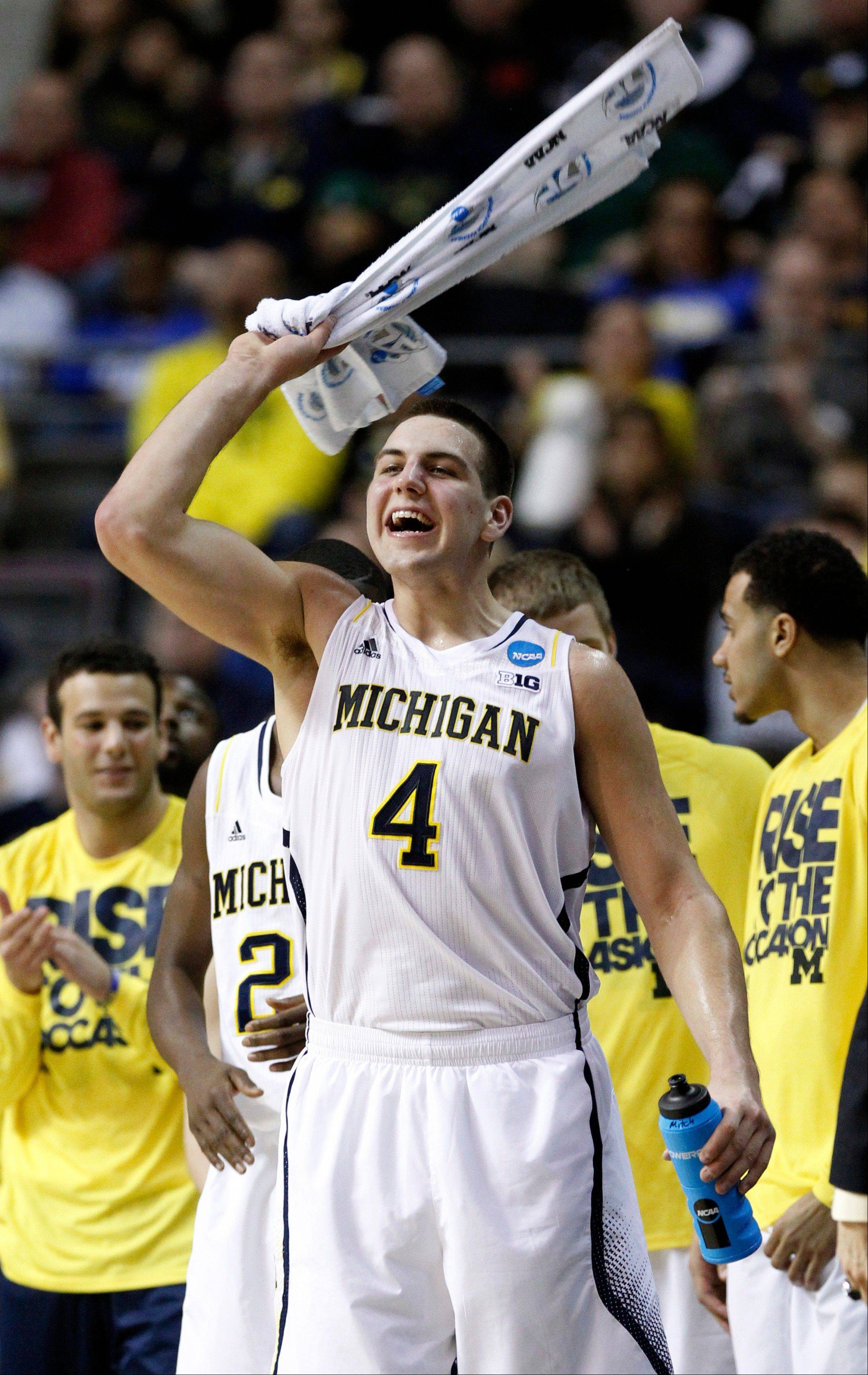 Michigan forward Mitch McGary (4) cheers on his teammates in the final minutes of their 71-56 win over South Dakota State in a second-round game of the NCAA men's college basketball tournament Thursday, March 21, 2013, in Auburn Hills, Mich.