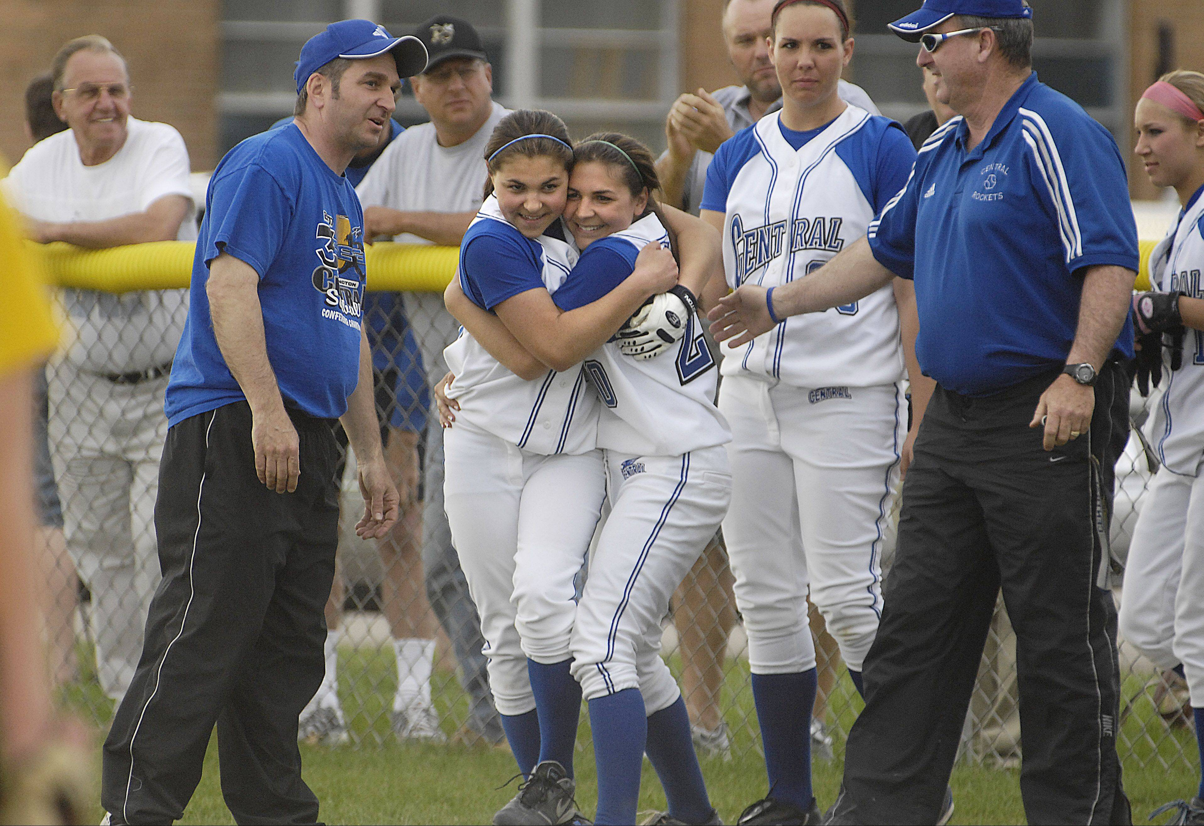 Erica Maisto, right, is hugged by her sister Jordan after Erica set the Burlington Central career pitching wins record in 2008. At far left is their dad, Wade, an assistant coach then who has now taken over the program again that he was head coach of from 1984-1998.
