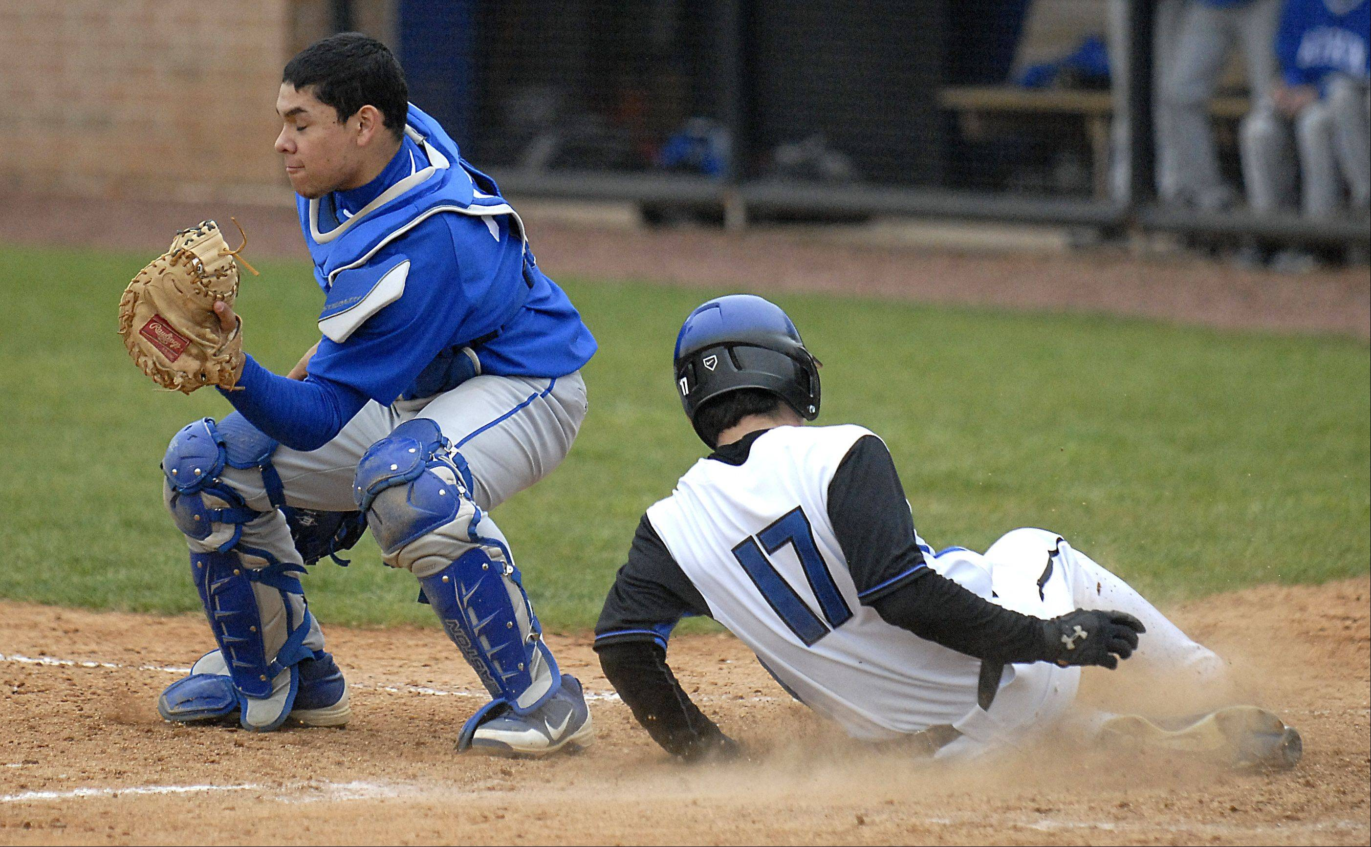 St. Charles North's Erik Nelson slides safely into home before Larkin catcher Niko Morado can tag him out during a game last season.