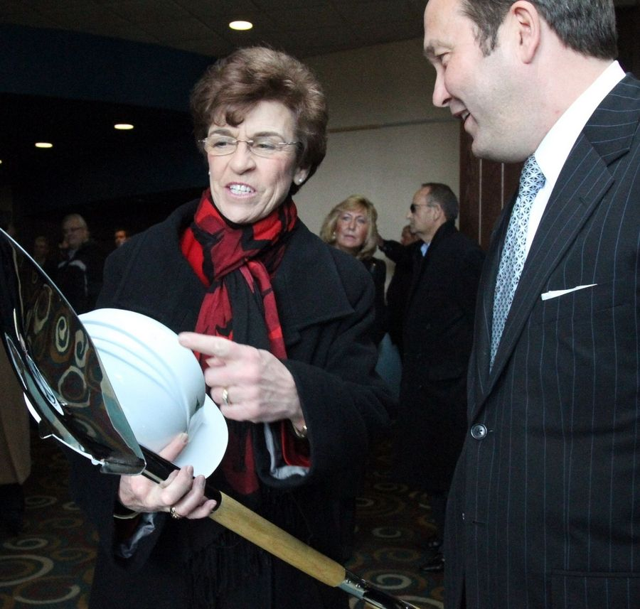 Arlington Heights Mayor Arlene Mulder jokes about using a groundbreaking shovel given to her by David Trandel, owner of the project, for gardening when she retires in April.