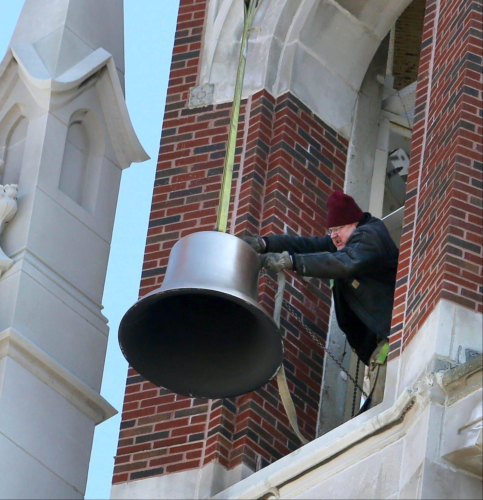 Crews hoist a bell into the tower at Ss. Peter and Paul Catholic Church in Naperville.