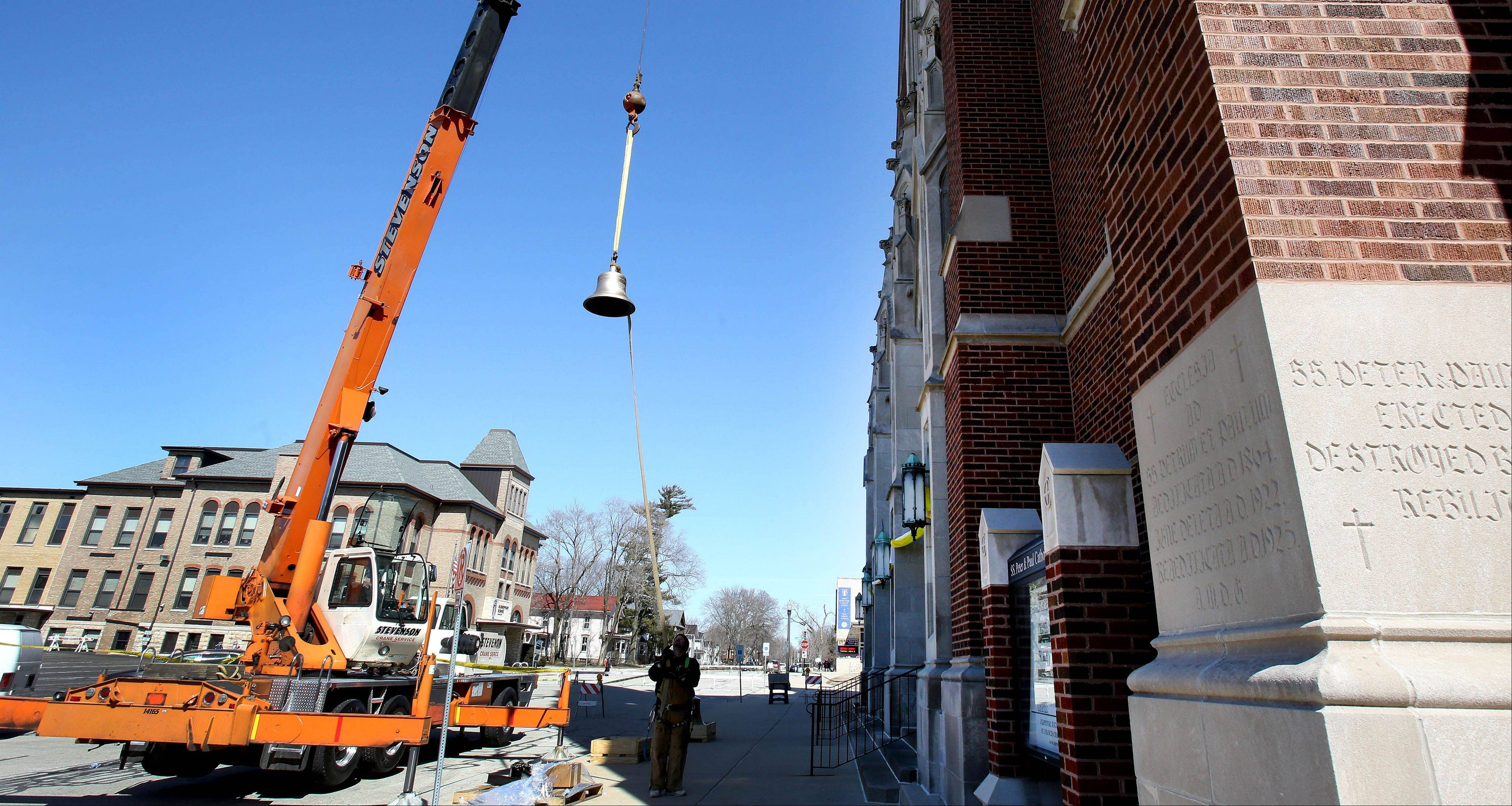 Crews hoist a bell into the tower at Ss. Peter and Paul Catholic Church in Naperville. The 167-year-old church has restored two of its bells and added a third. They'll all ring together for the first time over Easter weekend.
