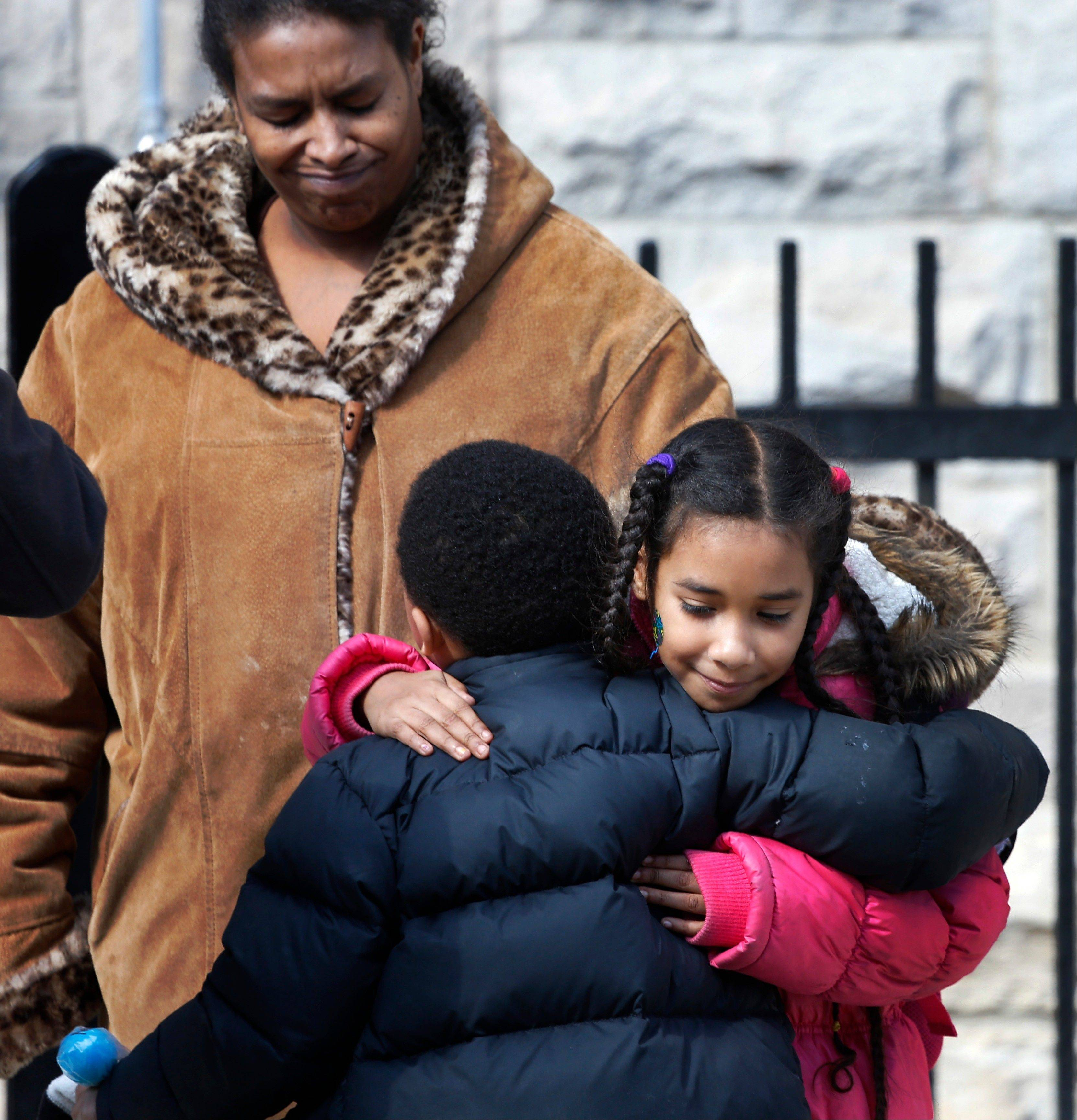 Maria Llanos, left, watches as her daughter Xochilt Fernandez hugs a fellow student Thursday at Lafayette Elementary in Chicago. Chicago Public Schools officials plan to close Lafayette and 53 other schools.