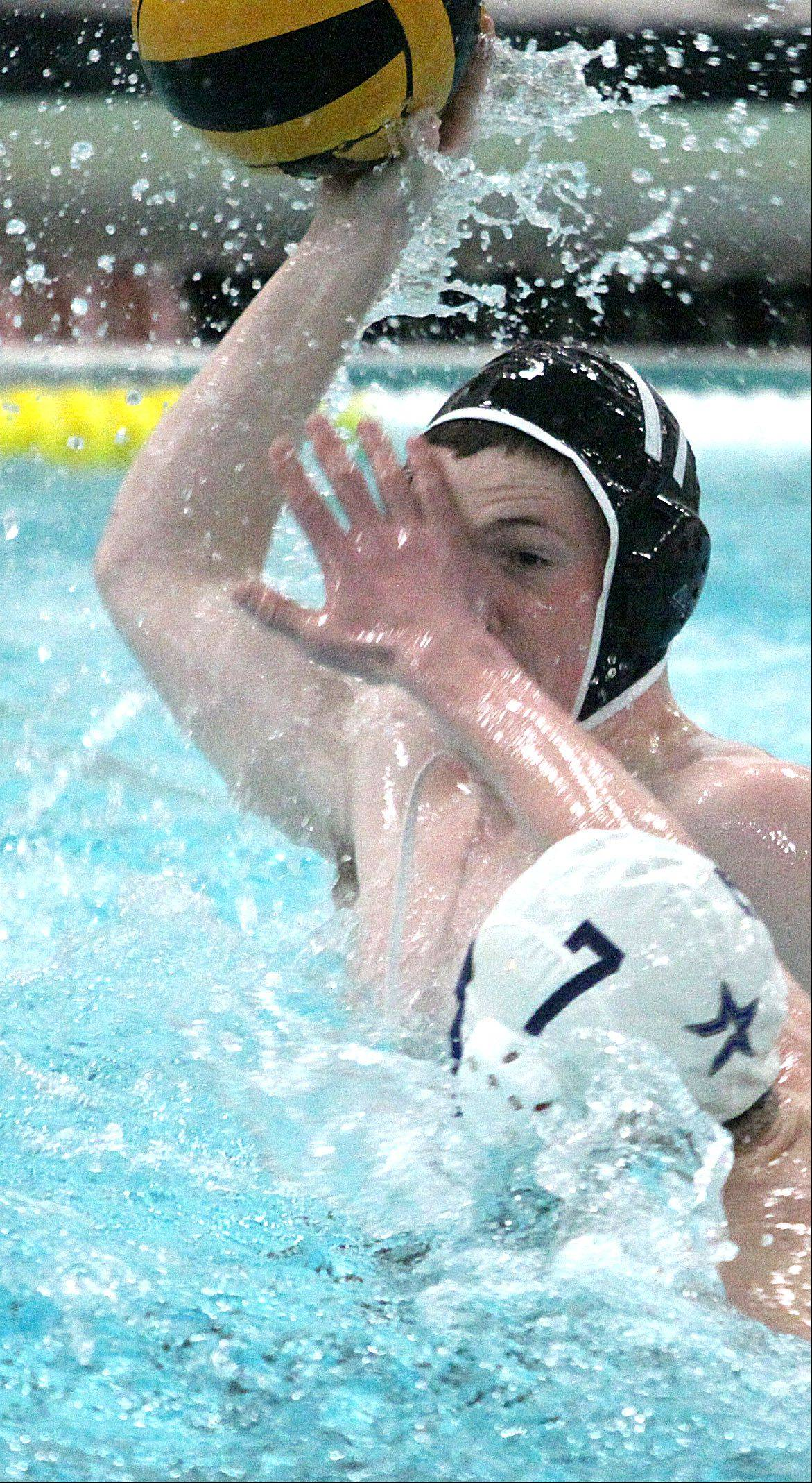 St Charles East's Max Schmitt prepares for a shot on goal under pressure from St Charles North's Nathan Bawolek, front, during a varsity water polo game at John Baker Norris Recreation Center on Thursday night.
