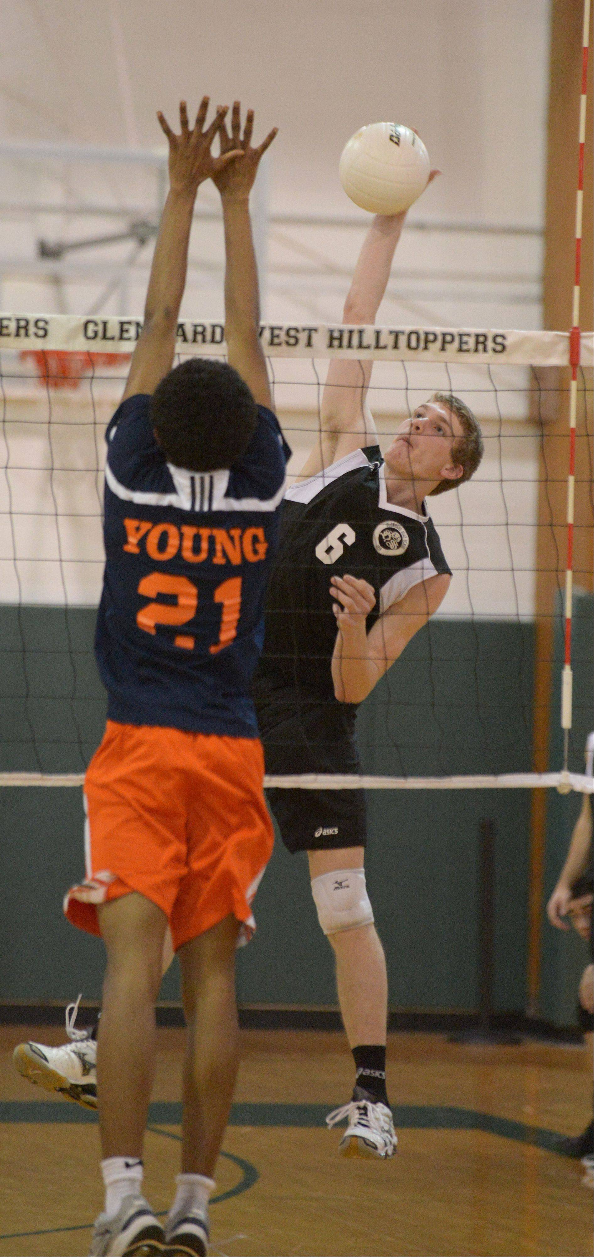 Max Montgomery of Glenbard West hits one at Malik Patton of Whitney Young. This took place during the Whitney Young at Glenbard West boys volleyball game Thursday.