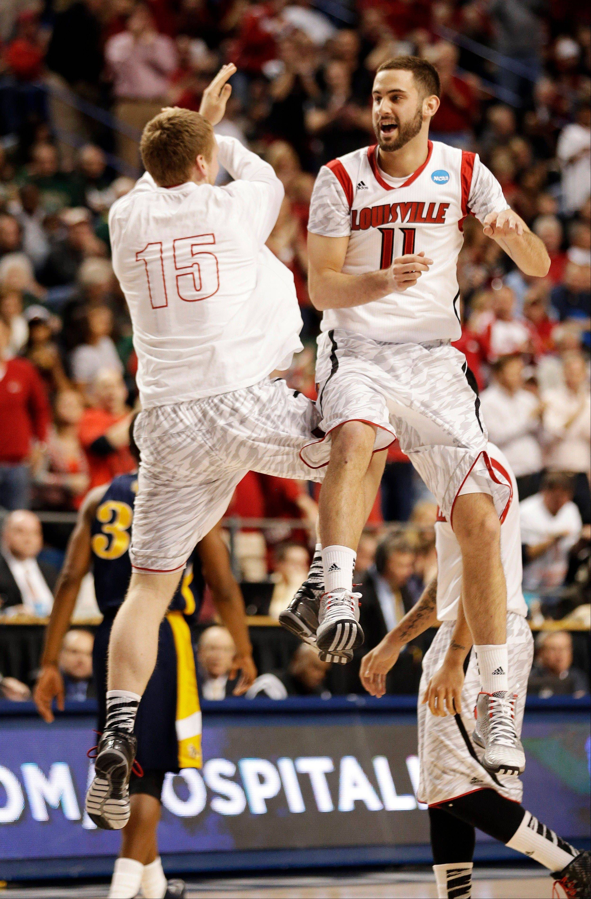 Louisville's Luke Hancock (11) and Tim Henderson (15) celebrate during the second half of a second-round game in the NCAA college basketball tournament against the North Carolina A&T Thursday, March 21, 2013, in Lexington, Ky.