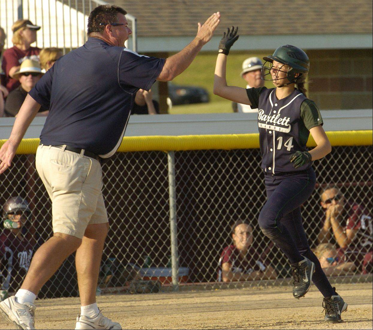 Bartlett's Alex Morales is greeted by Hawks' coach Jim Wolfsmith as she heads for home on Kayla Haberstich's home run in the seventh inning of Bartlett's Class 4A state semifinal win over Moline last season in East Peoria.