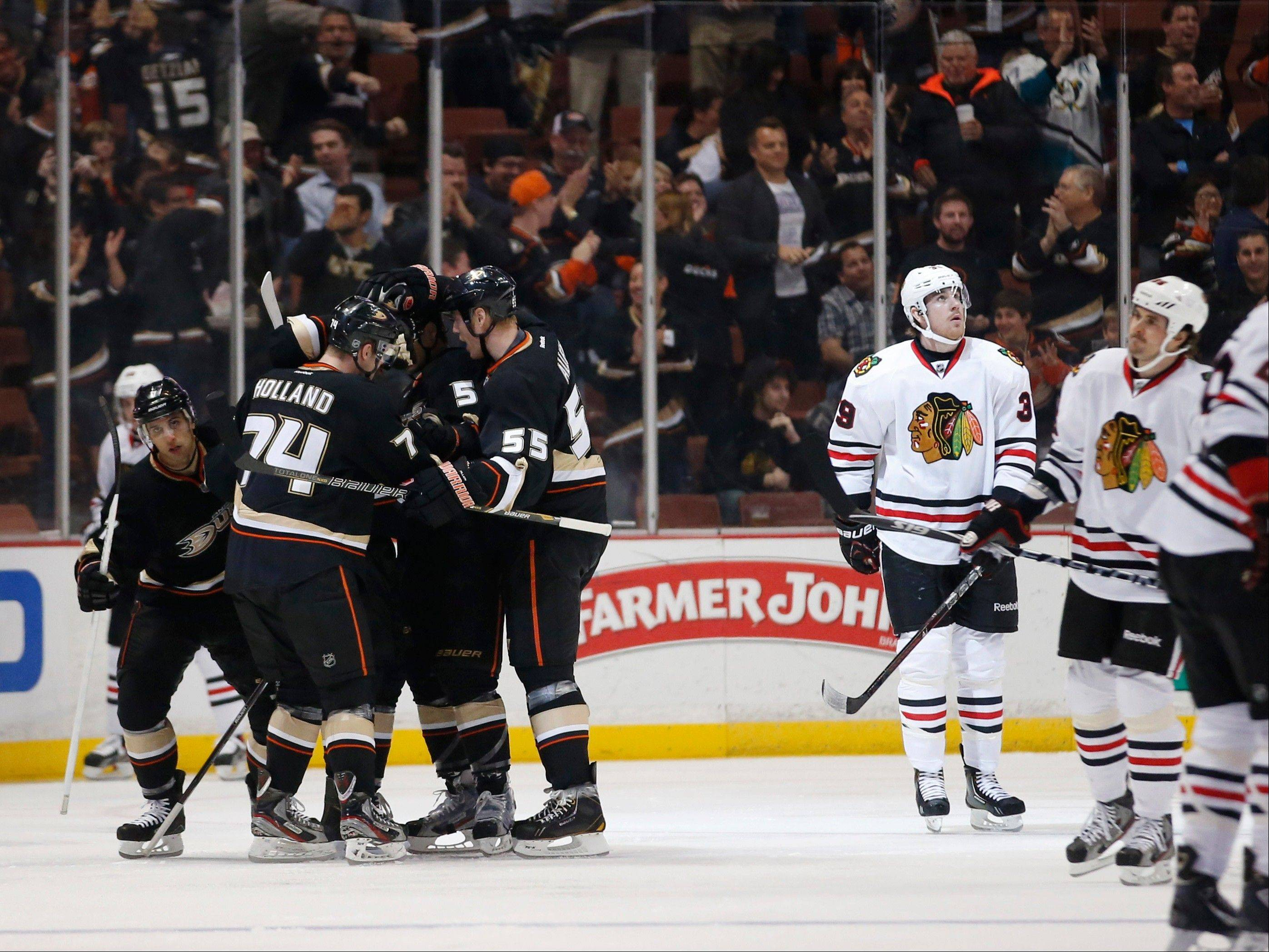 Anaheim Ducks' Peter Holland (74) is congratulated by Bryan Allen (55) and Luca Sbisa (5) after scoring a goal against the Chicago Blackhawks during the first period.