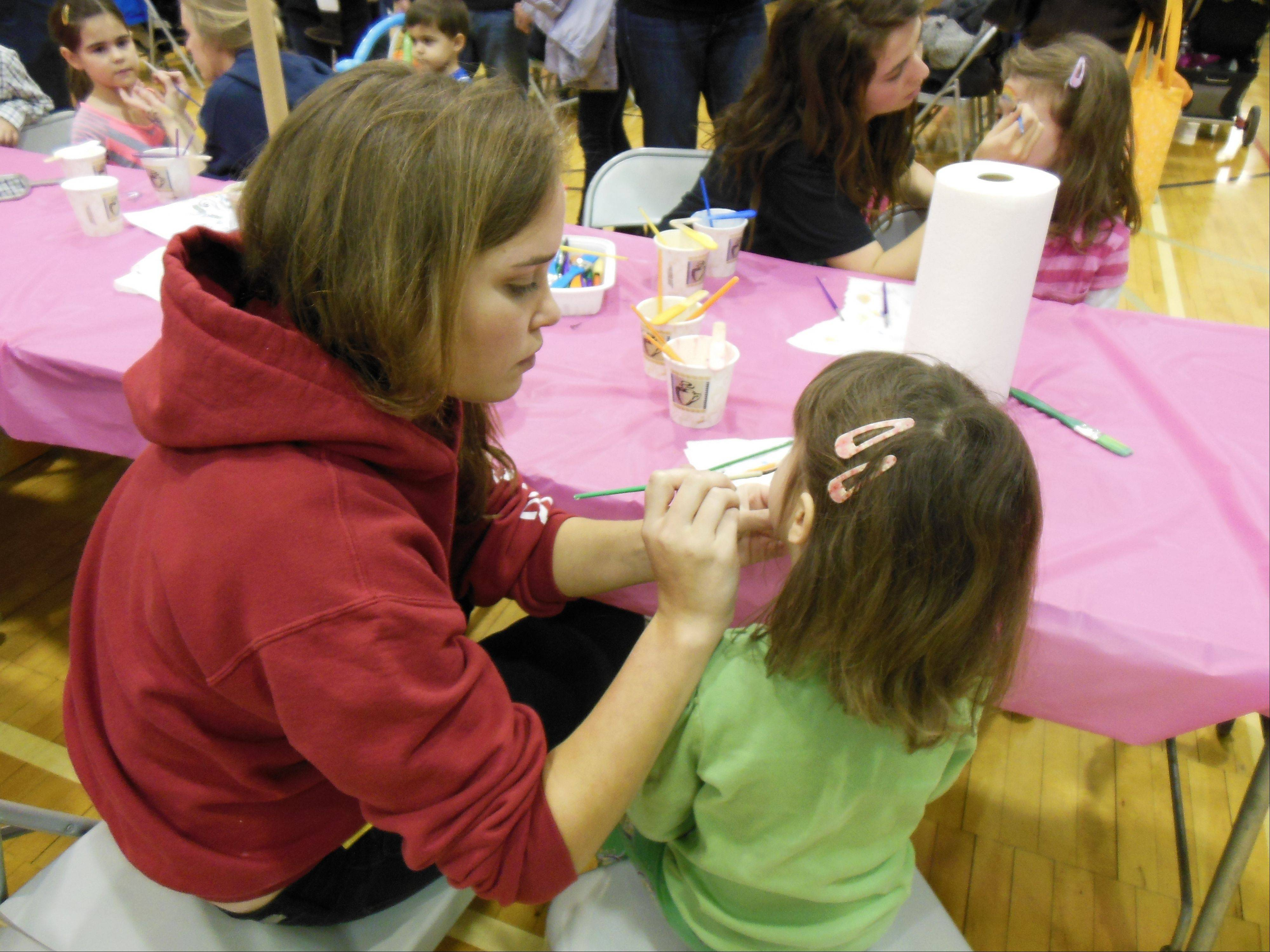 Junior Cathryn Rooney of Palatine decorates a child's face at the St. Viator Easter egg hunt, hosted by student council members, on March 17.
