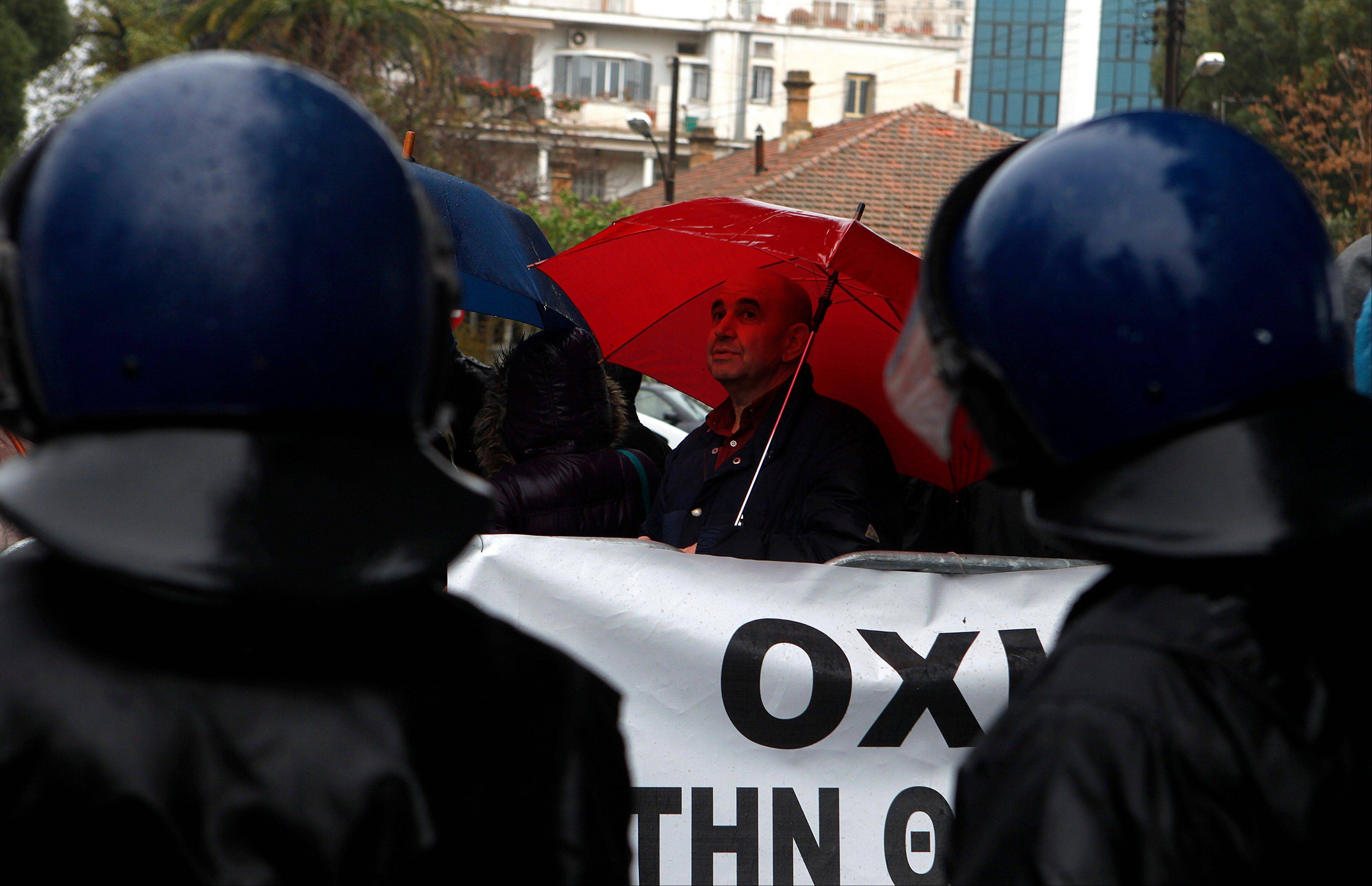 An employee of Laiki bank holding an umbrella is seen behind riot police during a rally outside of the parliament in capital Nicosia, Cyprus, Friday, March 22, 2013. Cypriot authorities were putting the final touches Friday to a plan they hope will convince international lenders to provide the money the country urgently needs to avoid bankruptcy within days.